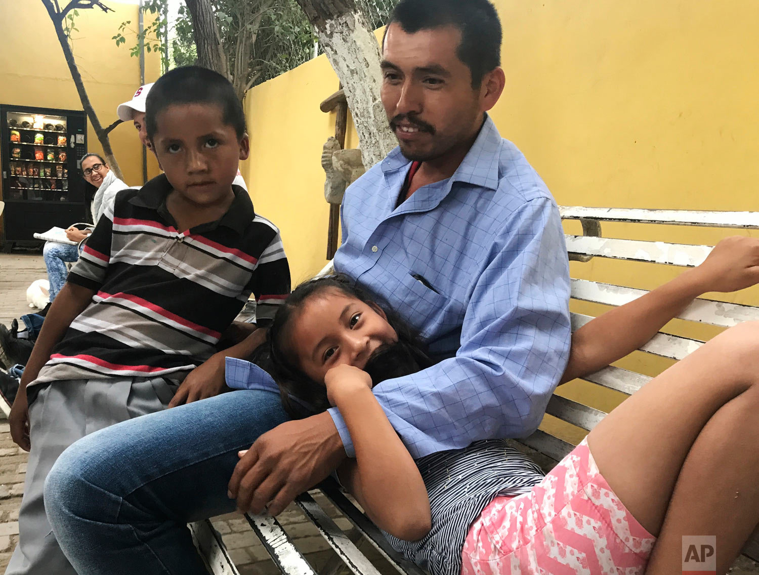 A father waits with his daughter and son in Piedras Negras, Mexico, as they seek asylum in the U.S., March 27, 2019. (AP Photo/Nomaan Merchant)