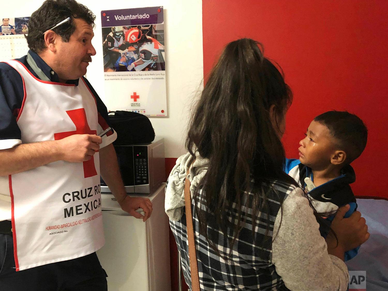 Mexican Red Cross-Cruz Roja Mexicana technician Marco Antonio Mendoza, left, helps a mother and her 3-year-old son in Nogales, Mexico, April 15, 2019. (AP Photo/Patricio Espinoza)