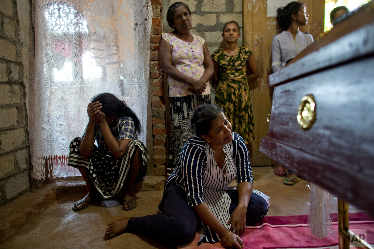 Relatives weep at the coffin with the remains of 12-year Sneha Savindi, who was a victim of Easter Sunday bomb blast at St. Sebastian Church reach home, Monday, April 22, 2019 in Negombo, Sri Lanka. The Easter Sunday bombings of churches, luxury hotels and other sites was Sri Lanka's deadliest violence since a devastating civil war in the South Asian island nation ended a decade ago. (AP Photo/Gemunu Amarasinghe)