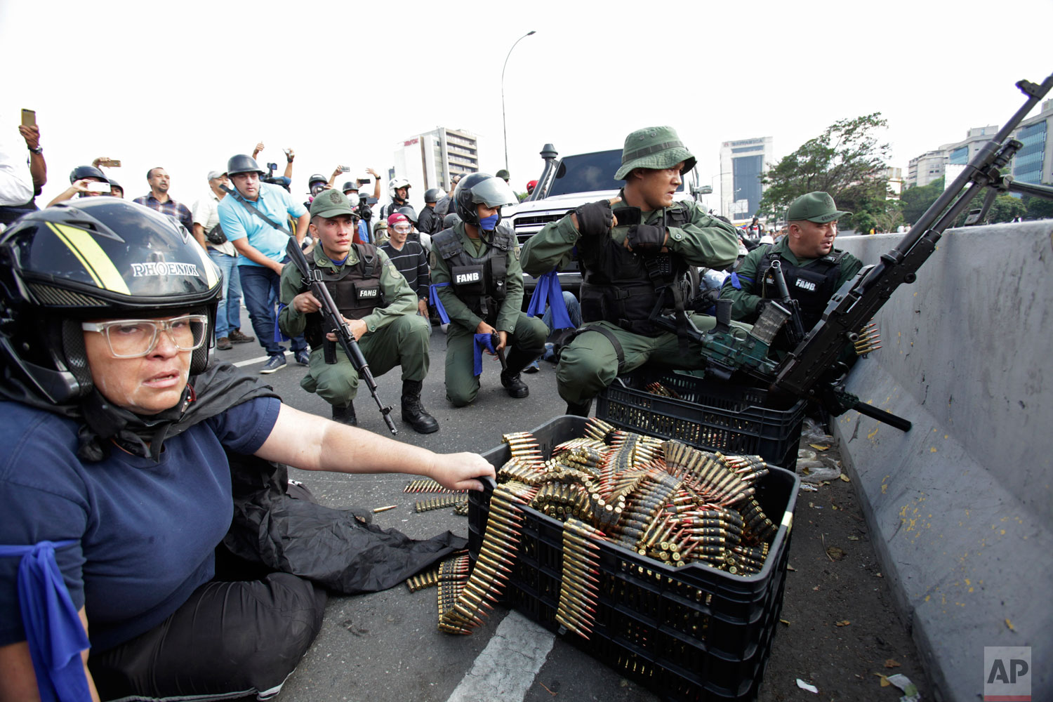 An anti-government protester sits by ammunition being used by rebel troops rising up against the government of Venezuela's President Nicolas Maduro as they all take cover on an overpass outside La Carlota military airbase where the rebel soldiers confront loyal troops inside the base in Caracas, Venezuela, Tuesday, April 30, 2019.   (AP Photo/Boris Vergara)