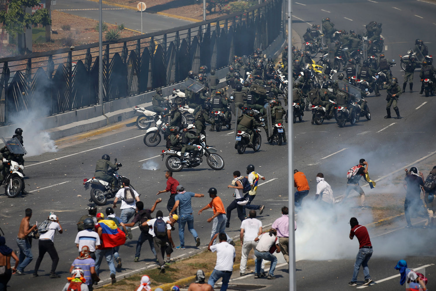 Opponents to Venezuela's President Nicolas Maduro confront loyalist Bolivarian National Guard troops firing tear gas at them, outside La Carlota military airbase in Caracas, Venezuela, Tuesday, April 30, 2019.  (AP Photo/Fernando Llano)