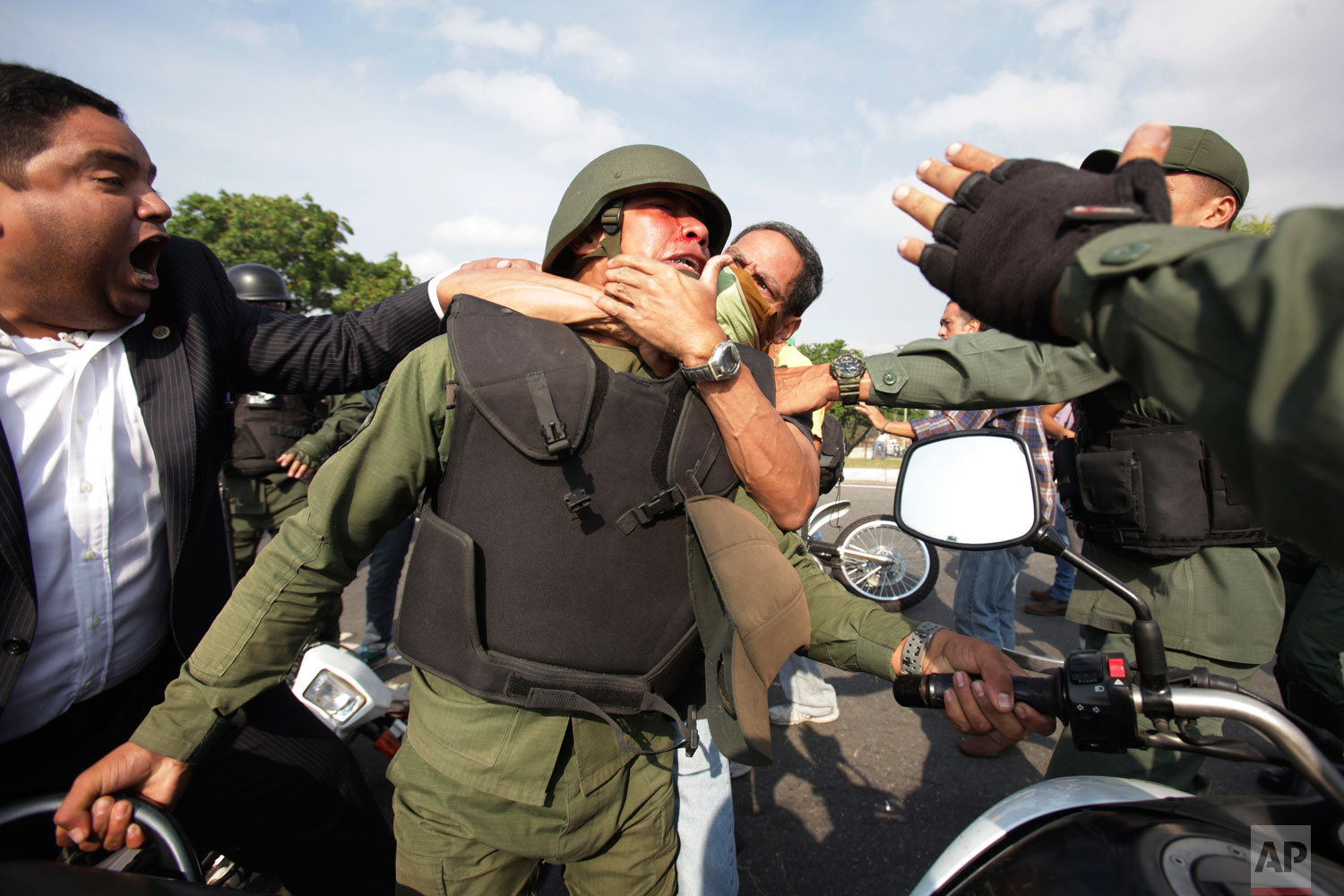 Opponents to Venezuela's President Nicolas Maduro, behind and left, scuffle with a National Guard who is loyal to President Nicolas Maduro during clashes with rebel soldiers attempting a military uprising outside La Carlota military airbase in Caracas, Venezuela, Tuesday, April 30, 2019. (AP Photo/Boris Vergara)