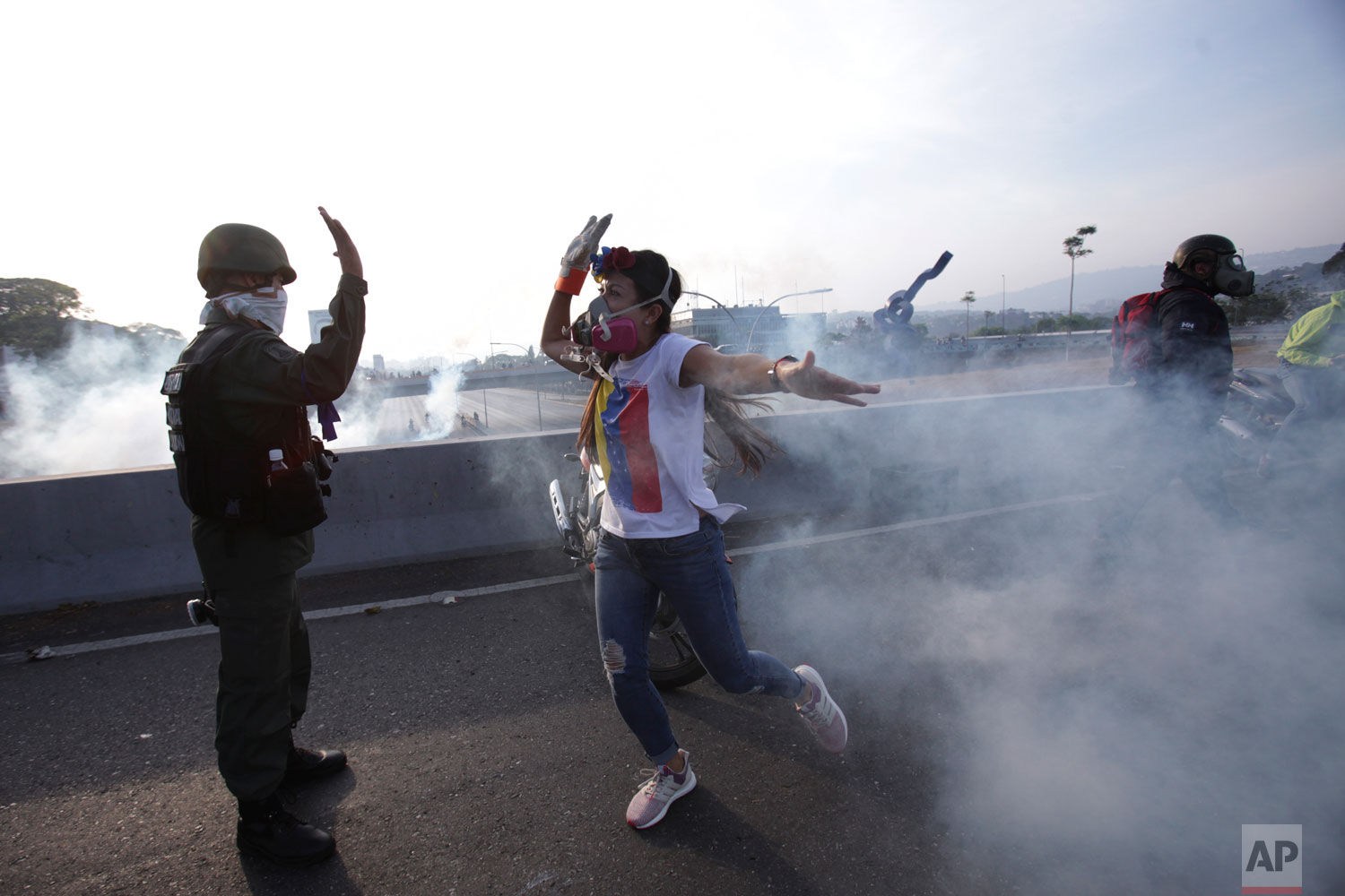An opponent to Venezuela's President Nicolas Maduro high fives a rebel soldier on a highway overpass outside La Carlota air base amid tear gas fired by loyalist soldiers from inside the base, early in what became a failed military uprising in Caracas, Venezuela, Tuesday, April 30, 2019. (AP Photo/Boris Vergara)