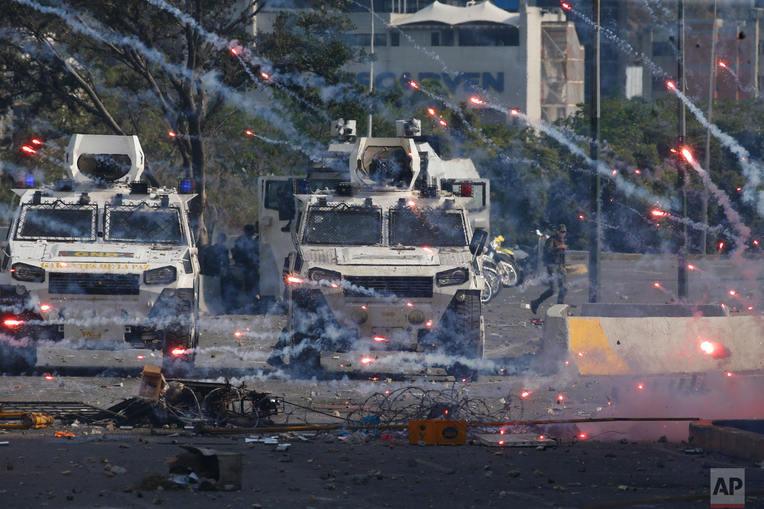 Fireworks launched by opponents of Venezuela's President Nicolas Maduro land near National Guard armored vehicles driven by soldiers loyal to Maduro, during a failed military uprising launched by opposition leader Juan Guaido in Caracas, Venezuela, Tuesday, April 30, 2019.  (AP Photo/Ariana Cubillos)