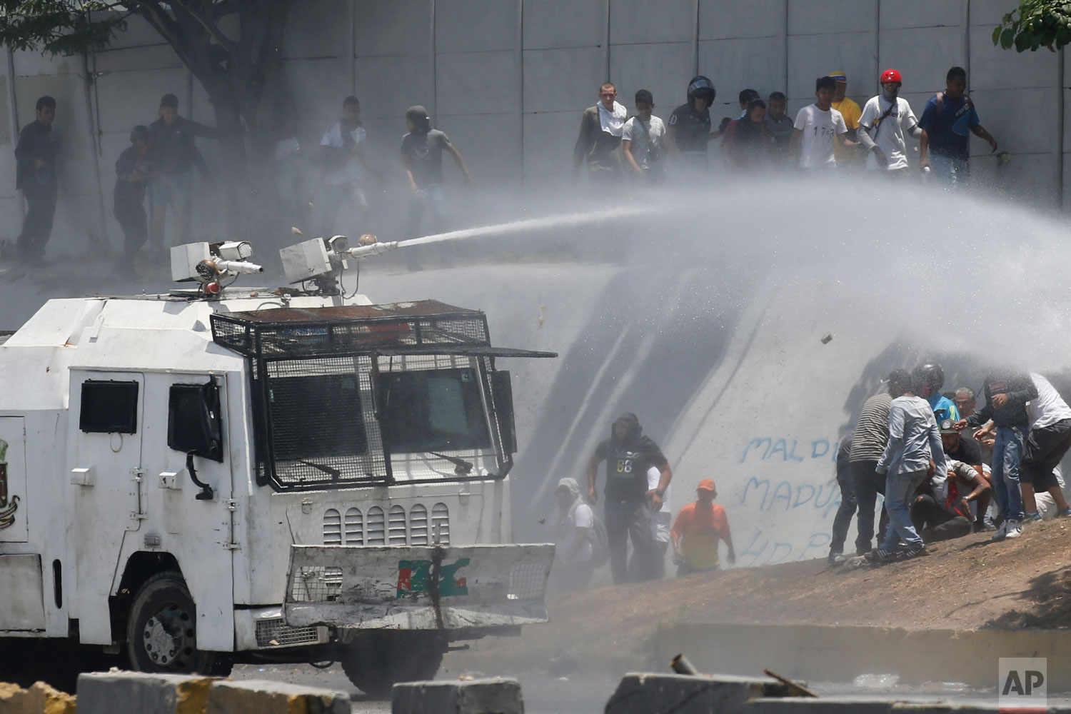 A National Guard water canon sprays opponents of Venezuela's President Nicolas Maduro during an attempted military uprising that eventually failed in Caracas, Venezuela, Tuesday, April 30, 2019. (AP Photo/Ariana Cubillos)