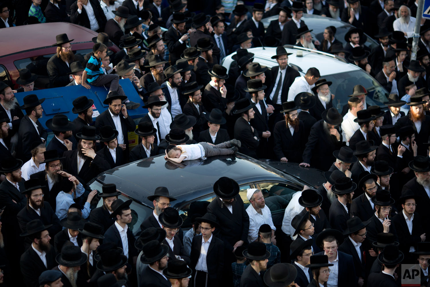 Ultra-Orthodox Jews watch the funeral procession of Rabbi of the Kaliv Hasidic dynasty and Holocaust survivor Menachem Mendel Taub during his funeral in Jerusalem, Sunday, April 28, 2019. Thousands attended the Jerusalem funeral of Menachem Mendel Taub, scion of a Hungarian rabbinic dynasty, who died aged 96. Taub helped produce a two-volume encyclopedia documenting Jewish religious martyrs killed in the Holocaust. His death came days before Israel marks Holocaust Remembrance Day, honoring six million Jews killed by Nazi Germany. (AP Photo/Ariel Schalit)
