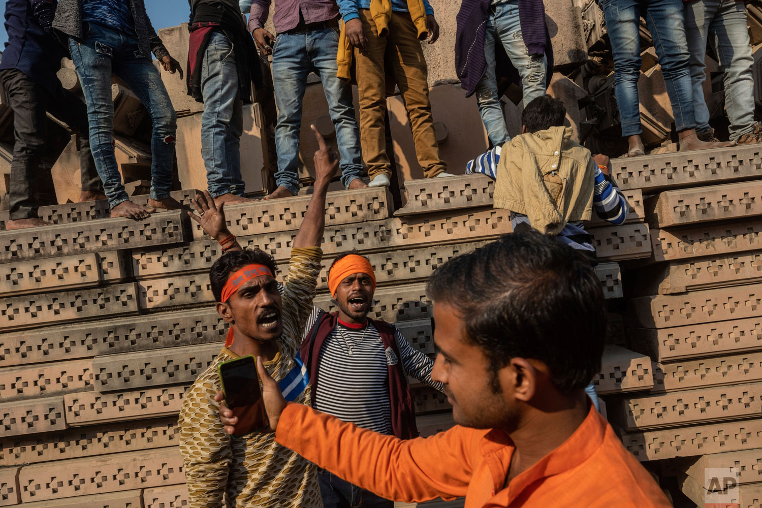 In this Sunday, Nov. 25, 2018 photo, Hindu hardliners gather next to building materials to be assembled in a temple dedicated to Hindu god Ram in Ayodhya, Uttar Pradesh, India. (AP Photo/Bernat Armangue)