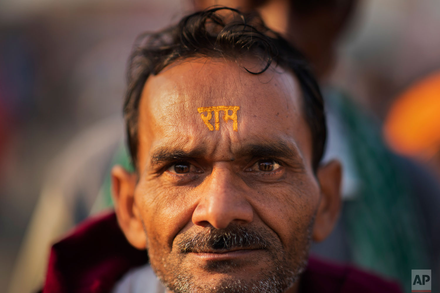 In this Sunday, Nov. 25, 2018 photo, a Hindu hardline supporter wears the the name of the god Ram written on his forehead in Ayodhya, Uttar Pradesh, India. Tens of thousands rallied to demand a Hindu temple be built on a site in northern India where hardliners in 1992 had attacked and demolished a 16th century mosque, sparking deadly Hindu-Muslim violence. Hindu groups say the mosque was built after a temple dedicated to Ram was destroyed by Muslim invaders. (AP Photo/Bernat Armangue)