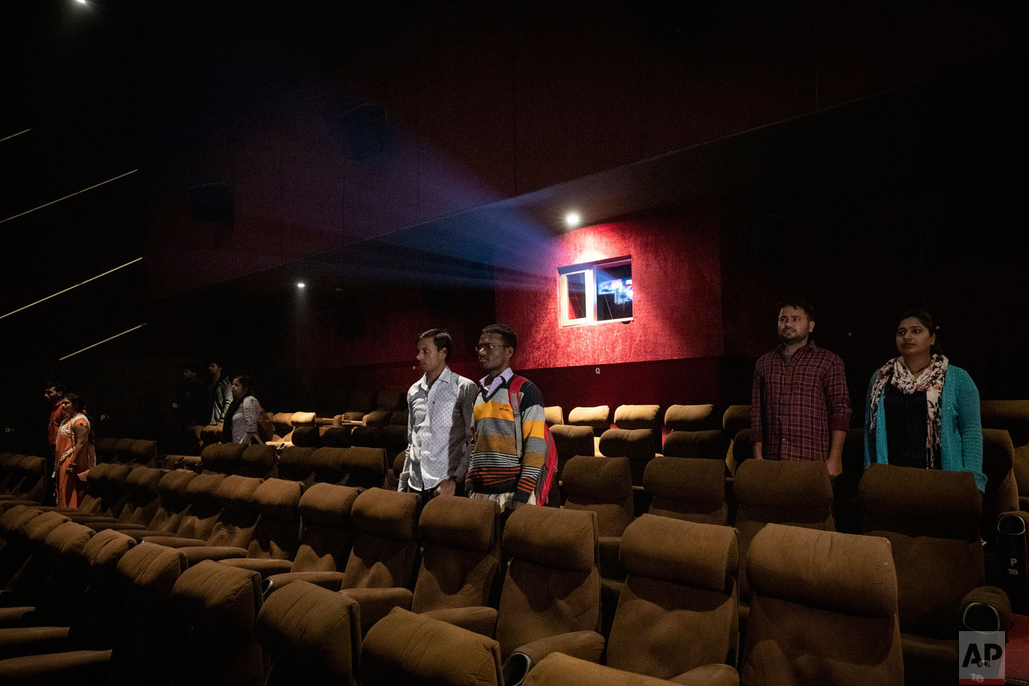 In this Monday, Nov. 26, 2018 photo, moviegoers stand as national anthem is played at a cinema before the screening of a movie in Lucknow, Uttar Pradesh, India. As with similar movements across the world, Hindu nationalism, once fringe, has now taken a central place in India's politics. (AP Photo/Bernat Armangue)