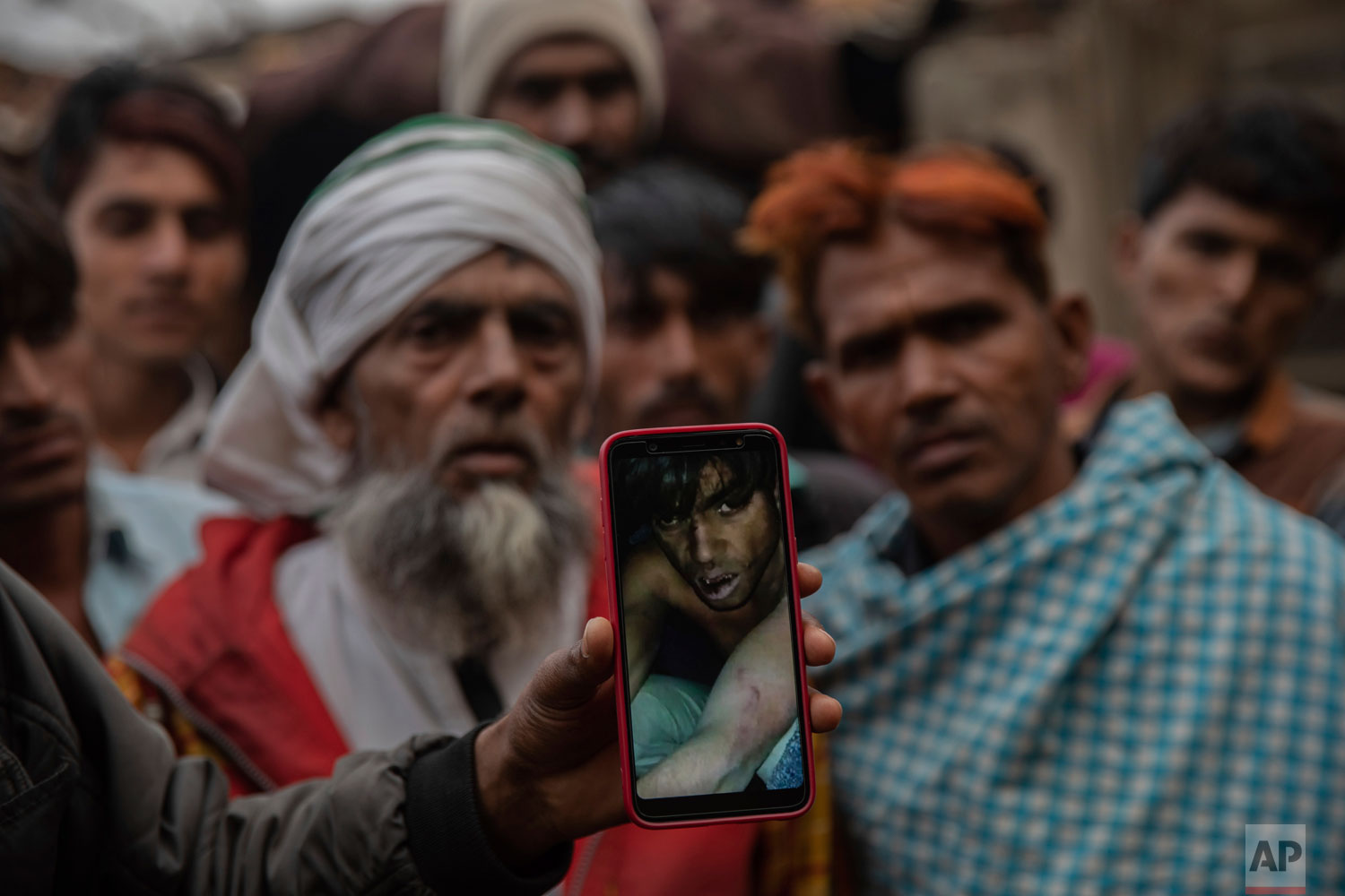 In this Tuesday, Jan. 22, 2019 photo, a man holds a phone showing a video of Muslim farmer Saghir Khan, 25, moments after being beaten, Mirzapur, India. Most of the attacks by so-called cow vigilantes from Hindu groups have targeted Muslims, who make up 14 percent of India's 1.3 billion people. Hindus make up about 80 percent of the population. (AP Photo/Bernat Armangue)