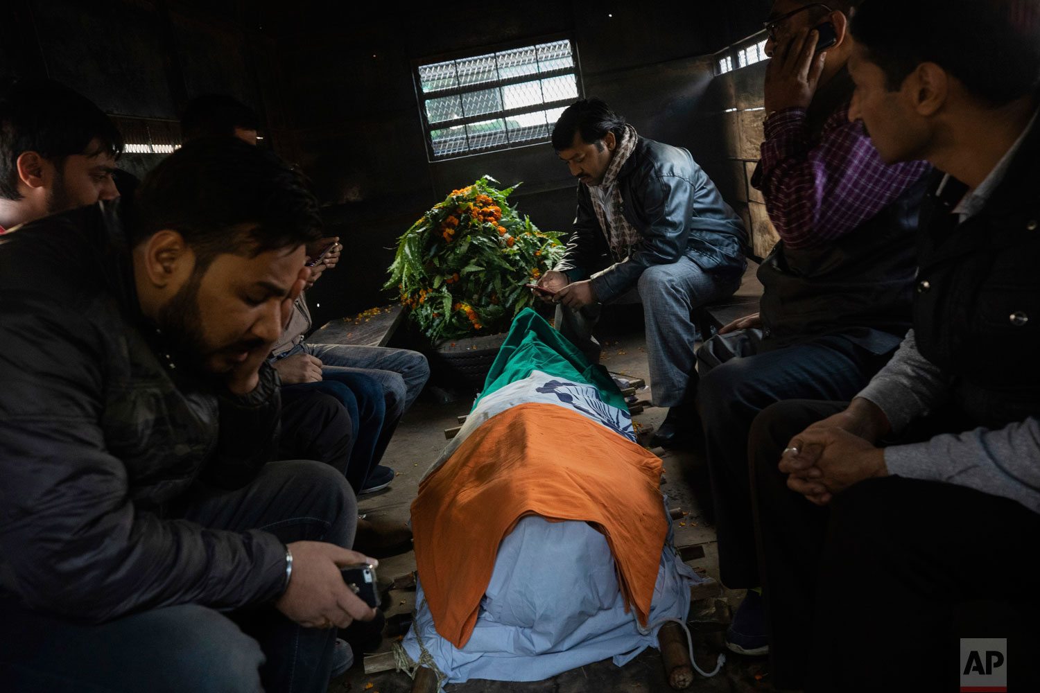 In this Tuesday, Dec. 4, 2018 photo, relatives cry next to the body of police Inspector Subodh Kumar Singh in Chingarwathi, near Bulandshahr, in the northern Indian state of Uttar Pradesh. The previous day, Singh and another person were killed in the mob violence that began with accusations of cow slaughter in the area. (AP Photo/Bernat Armangue)