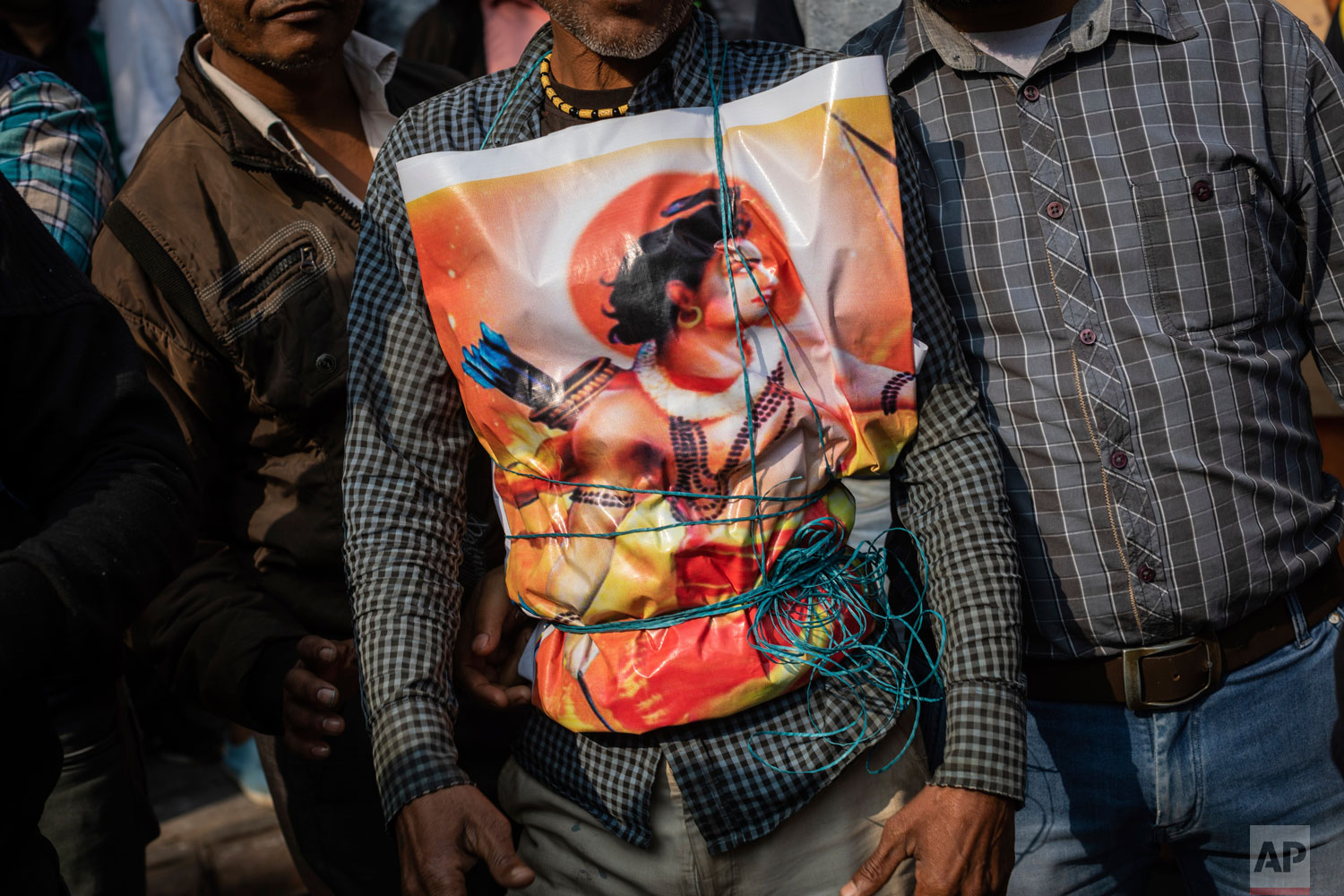 In this Sunday, Dec. 9, 2018 photo, a supporter of Hindu-extreme political group Vishwa Hindu Parishad wears a poster of the Hindu god Ram during a rally in New Delhi, India. (AP Photo/Bernat Armangue)