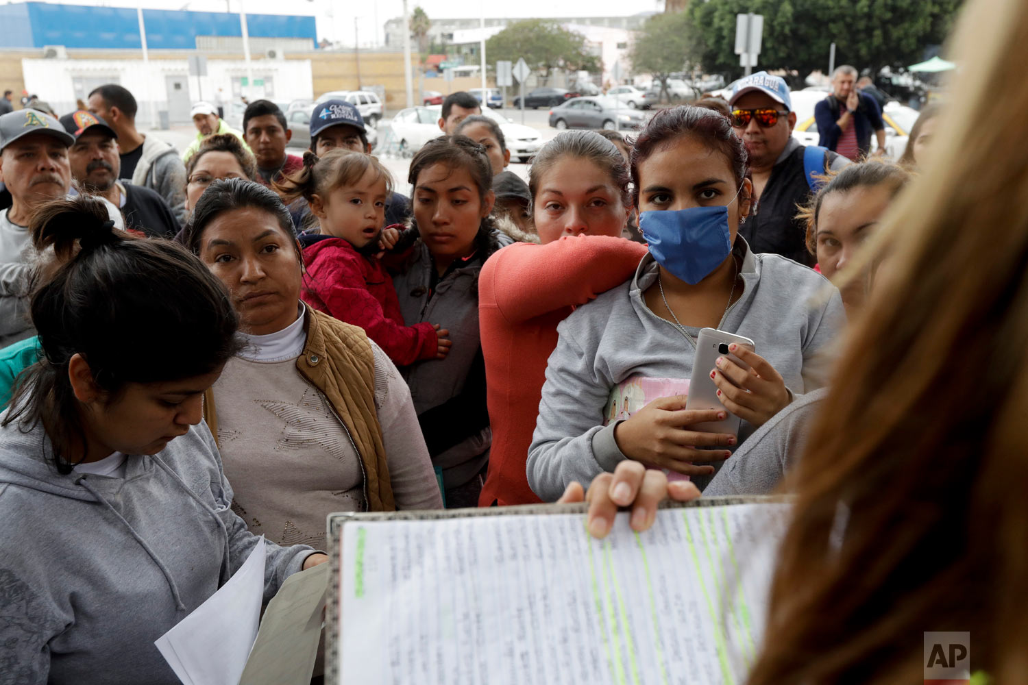 Women in Tijuana, Mexico, look on as numbers and names are called to from a list of asylum seekers. (AP Photo/Gregory Bull)