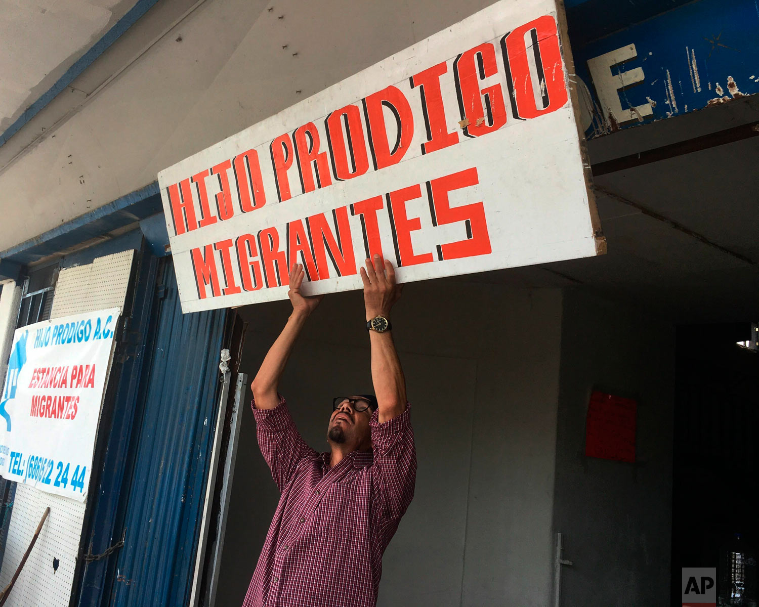 In this May 5, 2019, photo, Bernabe Rivera hoists a sign over a migrant shelter he manages in Mexicali, Mexico. (AP Photo/Elliot Spagat)
