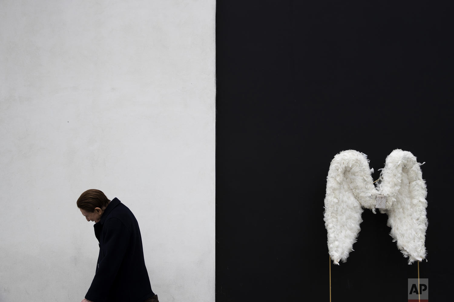 A man walks by a pair of angel wings as part of a store display in Beverly Hills, Calif., on Tuesday, May 7, 2019 (AP Photo/Jae C. Hong)