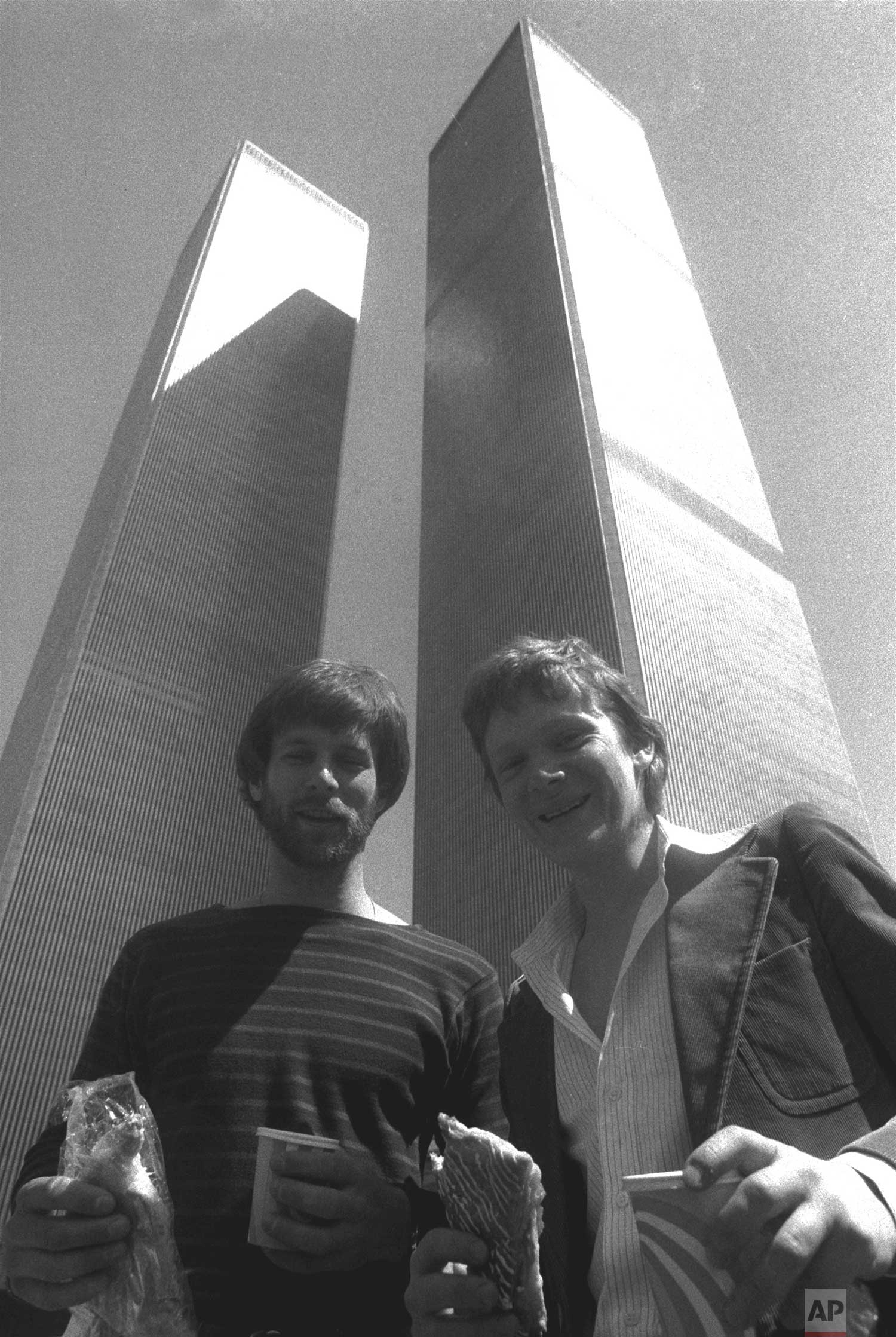 George Willig, left, and Philippe Petit prepare to catch a bite at the base of New York's twin World Trade Center Towers Wednesday, April 12. The two adventurers are more familiar with the skyscrapers from a different perspective; Petit for his tight rope walk between the two buildings, and Willig for his facade-climbing journey up the 110-story building last year. (AP Photo/Dave Pickoff)