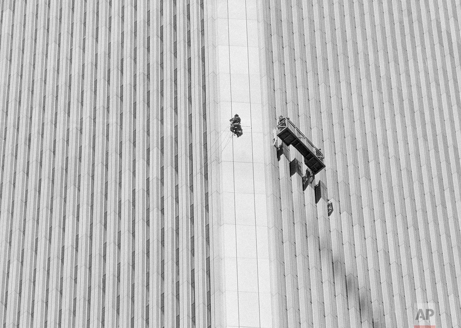 Using an invention he fashioned himself, George Willig heads for the quarter mile-high top of New York's World Trade Center, May 26, 1977. Thousands of spectators thronged the streets below to watch the 27-year-old amateur mountaineer in the 1,350-foot climb. (AP Photo/Dave Pickoff)