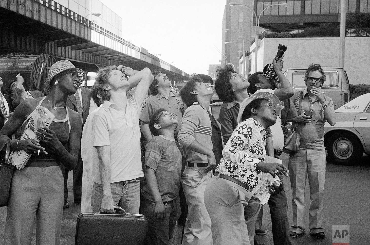 People watch George Willig, aerial daredevil, ascend the base of the World Trade Center in New York, May 26, 1977. (AP Photo/Carlos Rene Perez)