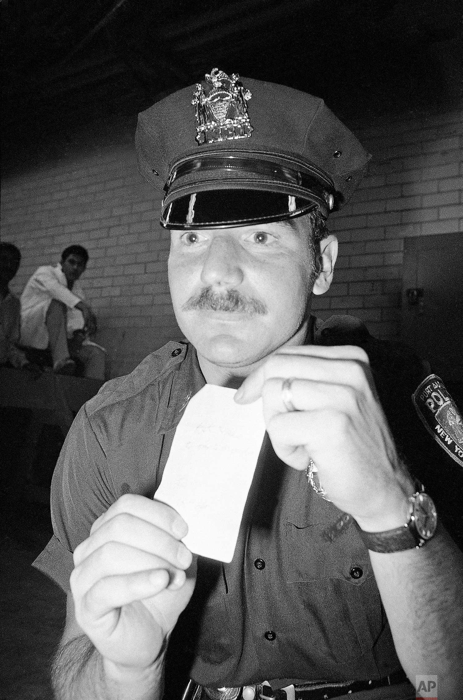 Officer Glenn Kildare with an autograph he received from George Willig in New York, May 26, 1977. (AP Photo/Carlos Rene Perez)