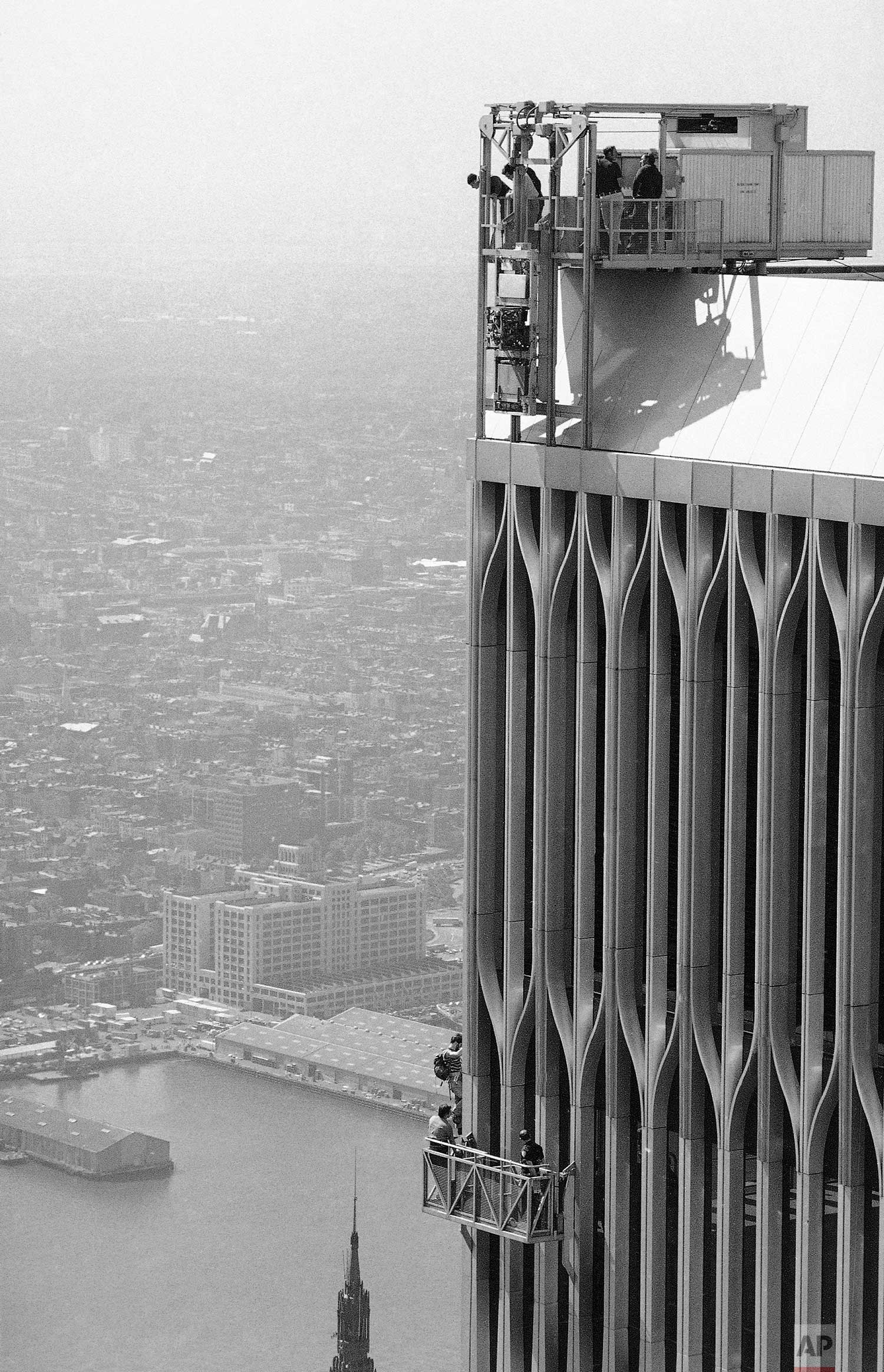 George Willig scales the World Trade Center tower as police follow him on a window washer's platform in New York, May 26, 1977. (AP Photo/Bob Eberle)