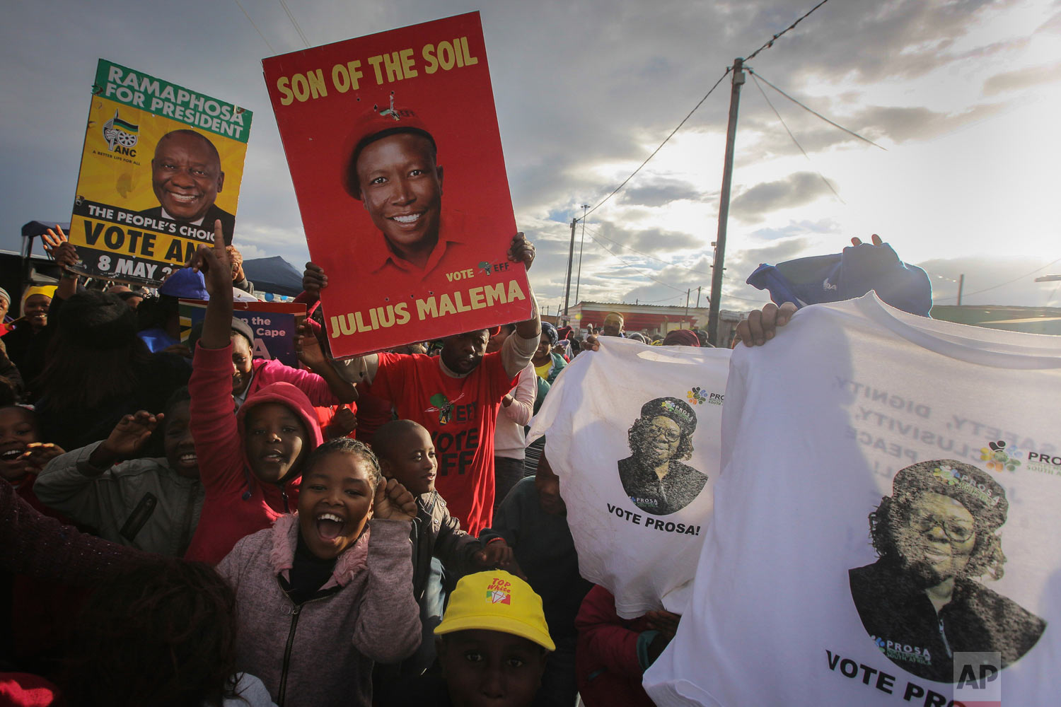 African National Congress (ANC) supporters, with green and yellow posters celebrate alongside rival Economic Freedom Fighters, (EFF) red posters, outside a voting station in Khayelitsha Township, Cape Town, South Africa, May 8, 2019. (AP Photo/Halden Krog)