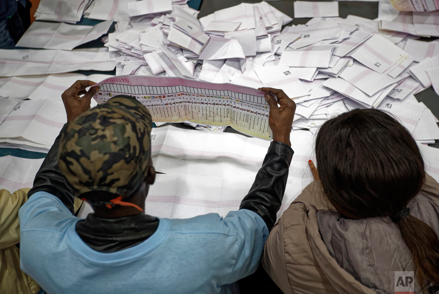 Electoral workers count ballots in view of party agents after the close of polls at the Parkhurst Primary School in Johannesburg, South Africa, May 8, 2019. (AP Photo/Ben Curtis)