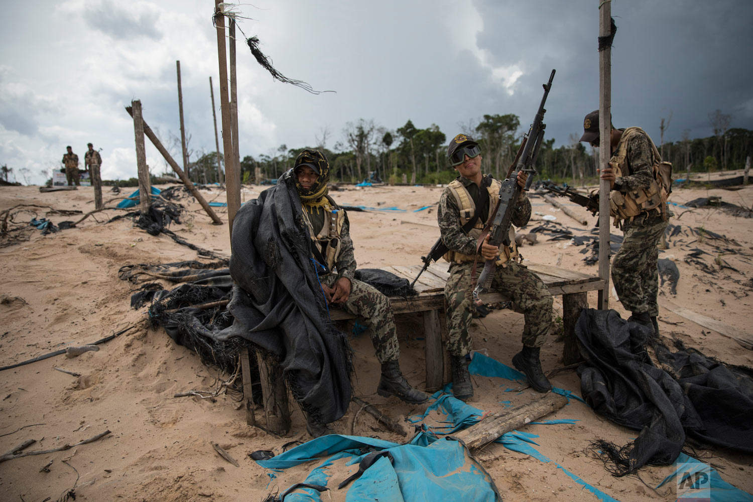 In this April 1, 2019 photo, soldiers wait for the arrival of a helicopter bringing supplies and replacements, on a makeshift airstrip of the Balata police and military base in Peru's Tambopata province. Peru has installed military bases in the province in hopes of curbing not just illegal mining but also human trafficking and other associated crimes. (AP Photo/Rodrigo Abd)