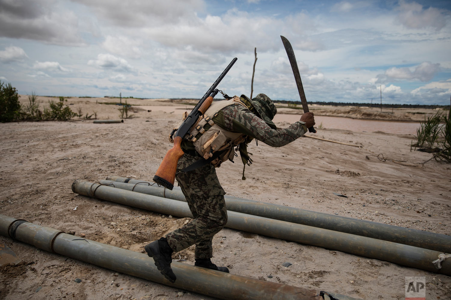 "A soldier hacks with a machete tubing used by illegal miners to mine gold, as part of ""Operation Mercury"" on March 27, 2019, in Peru's Tambopata province. (AP Photo/Rodrigo Abd)"