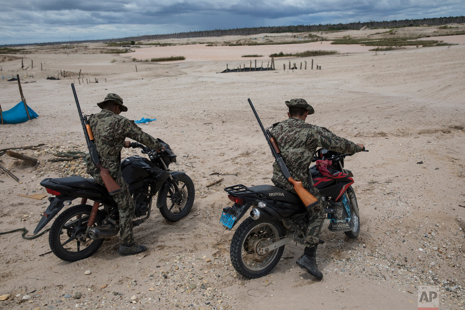 "In this March 27, 2019 photo, ""Operation Mercury"" soldiers patrol on motorbikes an area once used by illegal miners, in Peru's Tambopata province. Peruvian police and soldiers search for and destroy equipment used by illegal gold miners in a part of the Amazon rainforest where the mining transformed dense foliage into a desert pocked with dead trees and toxic pools. (AP Photo/Rodrigo Abd)"