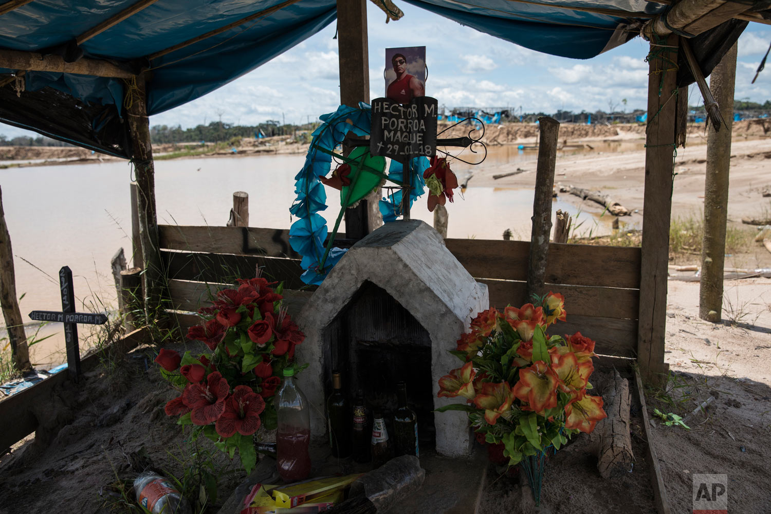 A memorial adorned with artificial flowers and bottles of alcohol inside a former illegal gold mining camp that has been occupied by special forces and converted into the Balata police and military base, March 28, 2019, in Peru's Tambopata province. The base now occupied by security forces is surrounded by two lakes contaminated with mercury, as well as debris left over by miners. (AP Photo/Rodrigo Abd)
