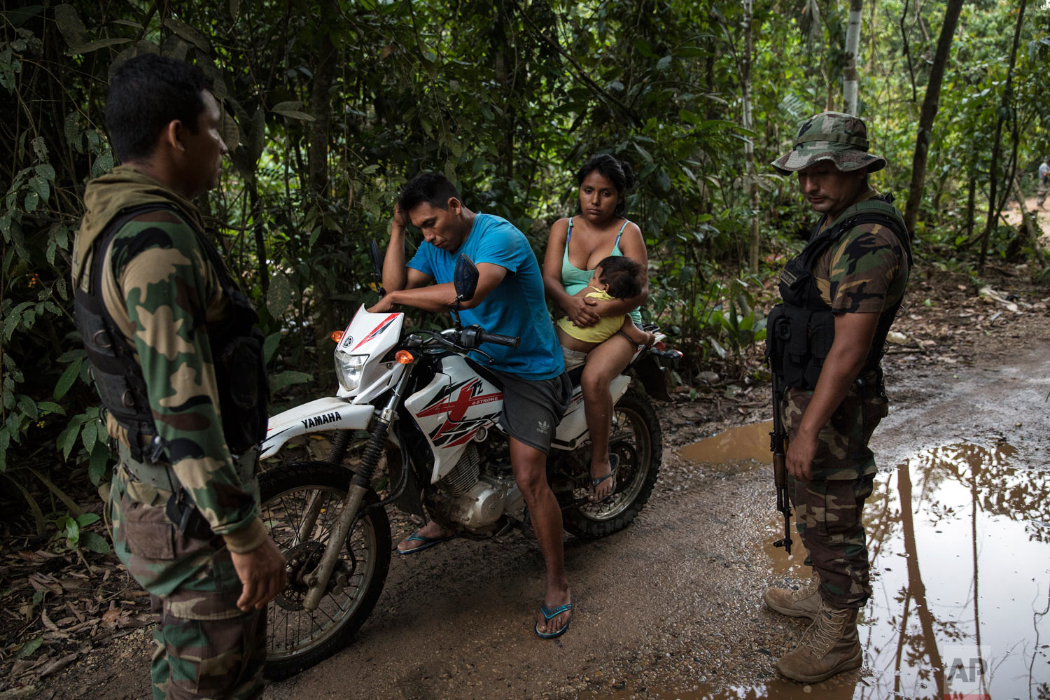 """Operation Mercury"" policemen question a wildcat miner near the Mega 12 police base in Peru's Tambopata province, April 3, 2019. The operation began in February when authorities evicted thousands of illegal gold miners from the area and deployed hundreds of police and soldiers for longer terms. (AP Photo/Rodrigo Abd)"