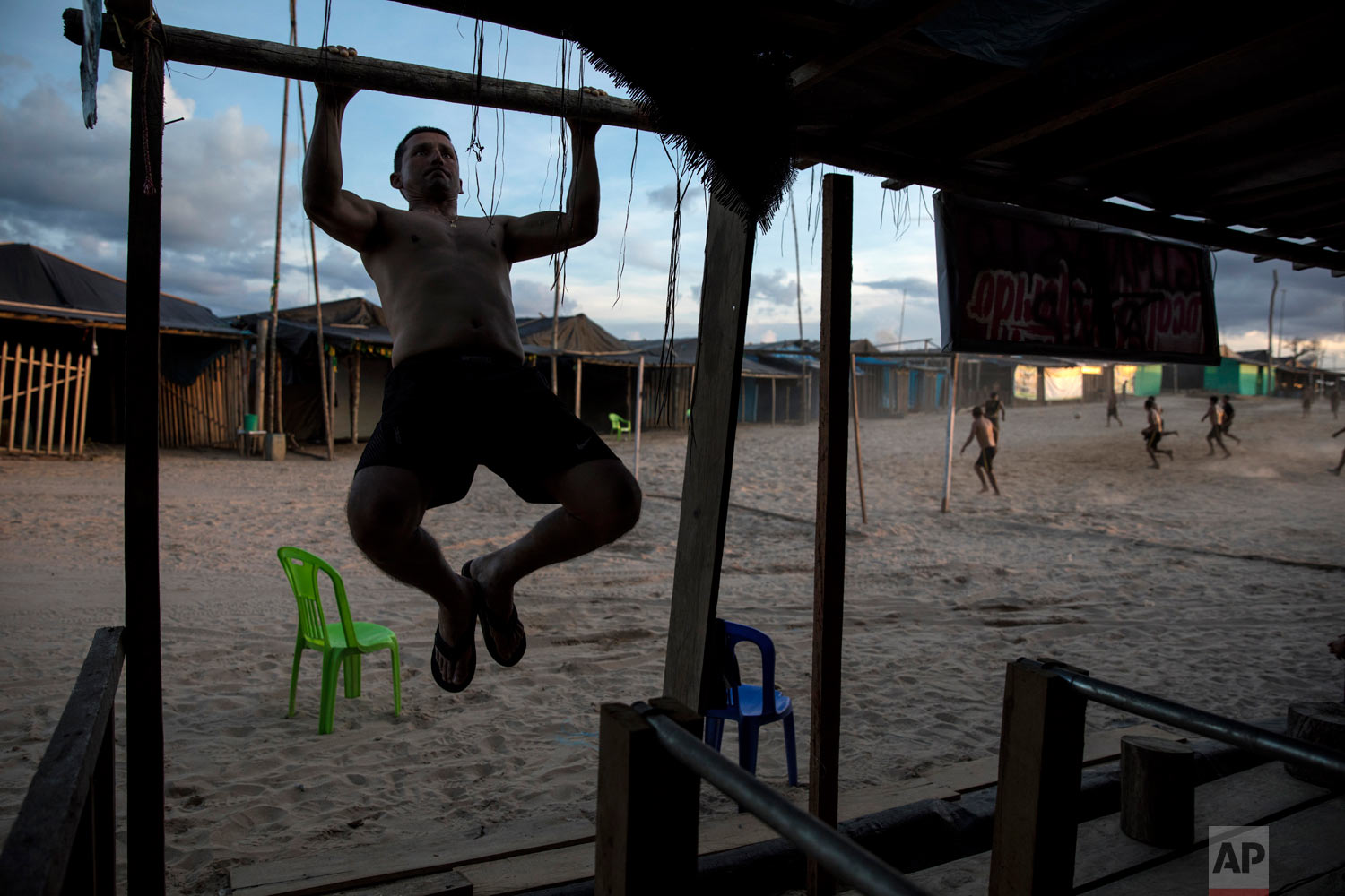 "Maj. Gustavo Cerdeña does pull-ups using the wood frame of a structure at the Balata police and military base, once an illegal gold mining camp, March 31, 2019, in Peru's Tambopata province. Cerdeña said he had come to the booming area before the start of ""Operation Mercury"", in February. ""It was full of people, it was like Gomorrah before it rained fire,"" he said, referring to the notorious city's destruction in the Bible. ""Now everything is quieter."" (AP Photo/Rodrigo Abd)"