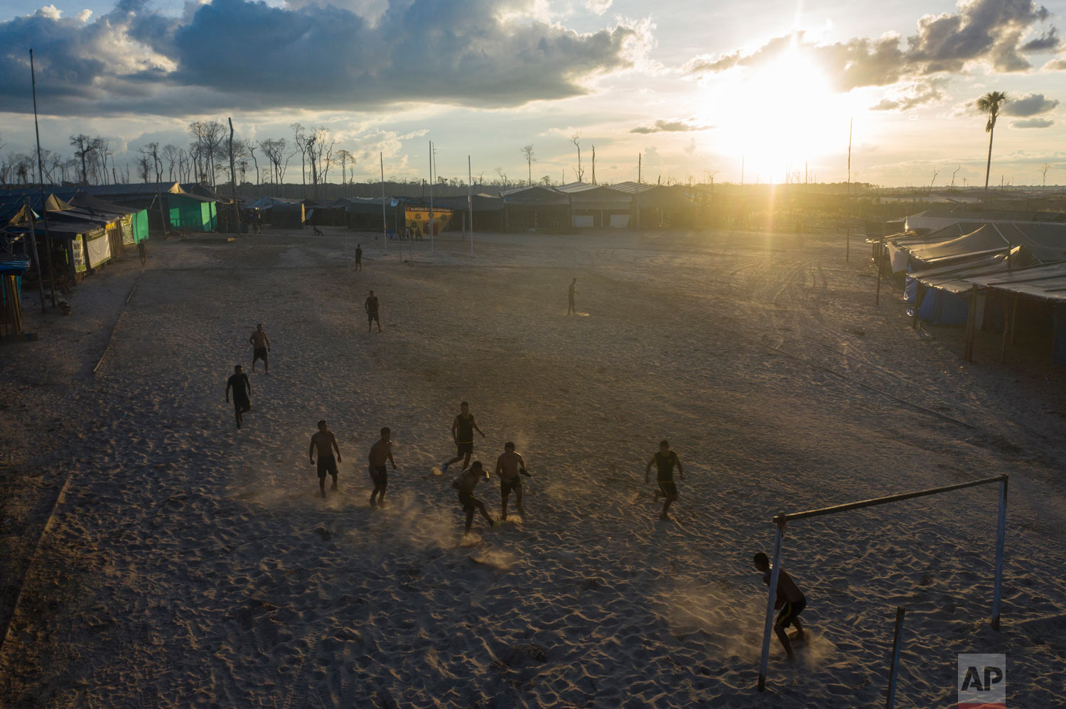 """Operation Mercury"" soldiers play soccer at the Balata police and military base, March 31, 2019, in Peru's Tambopata province. As night falls, they play cards, watch television and call family from their remote outpost. (AP Photo/Rodrigo Abd)"