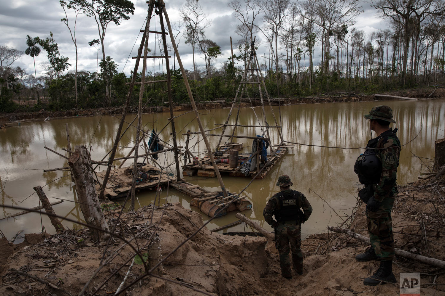"Police special forces stand next to illegal mining machinery, April 1, 2019, in Peru's Tambopata province. As part of ""Operation Mercury"", Peruvian police and soldiers search for and destroy equipment used by illegal gold miners in a part of the Amazon rainforest where the mining transformed dense foliage into a desert pocked with dead trees and toxic pools. (AP Photo/Rodrigo Abd)"