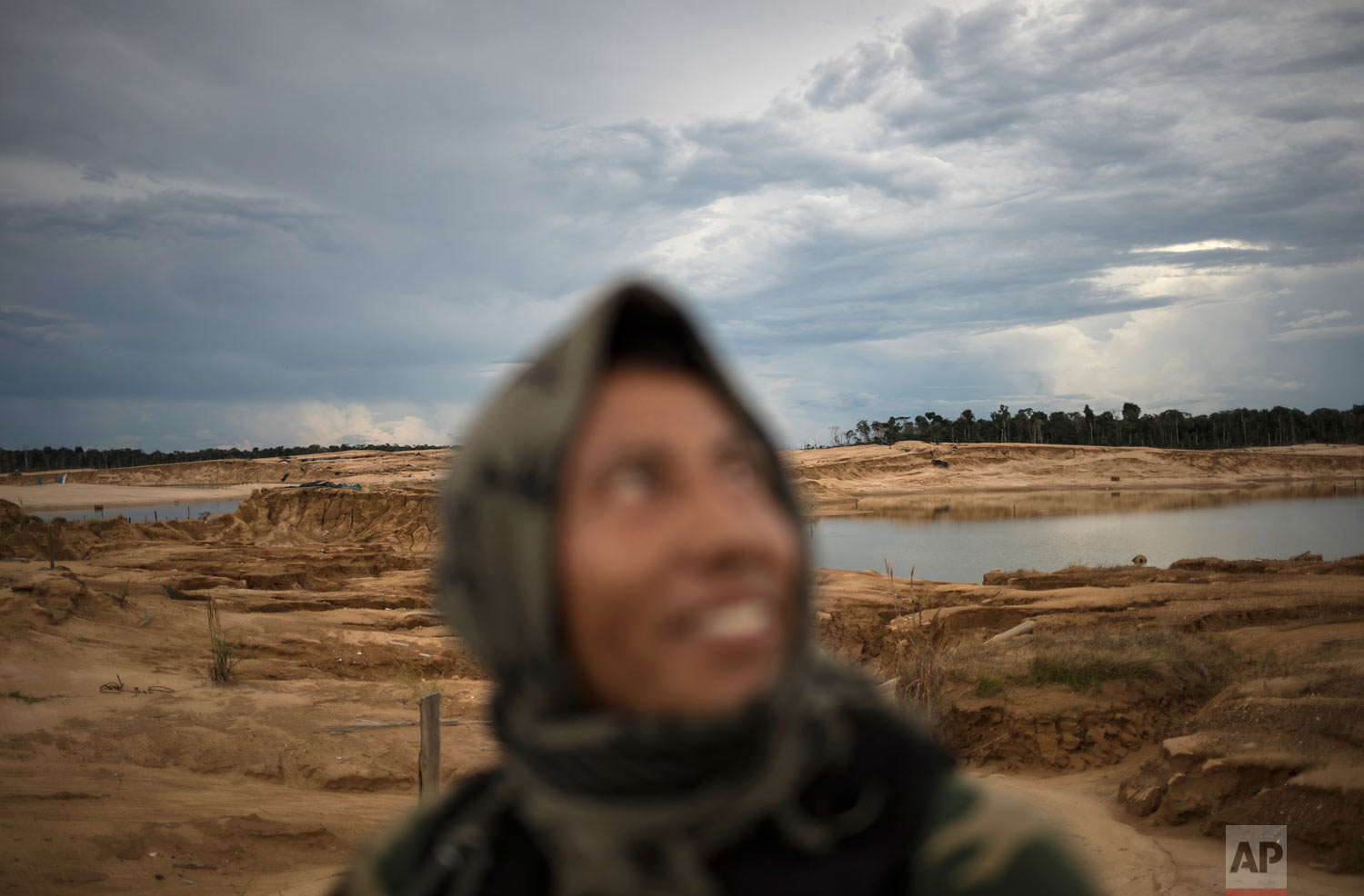 "A police officer smiles while riding in a pick-up truck, April 3, 2019, during a patrol in Peru's Tambopata province. The area known by miners as ""La Pampa,"" which surrounds a national park and doesn't appear on state maps, has yielded roughly 25 tons of illegally mined gold a year, much more than the legally produced amount in the same area, according to the Peruvian government. (AP Photo/Rodrigo Abd)"