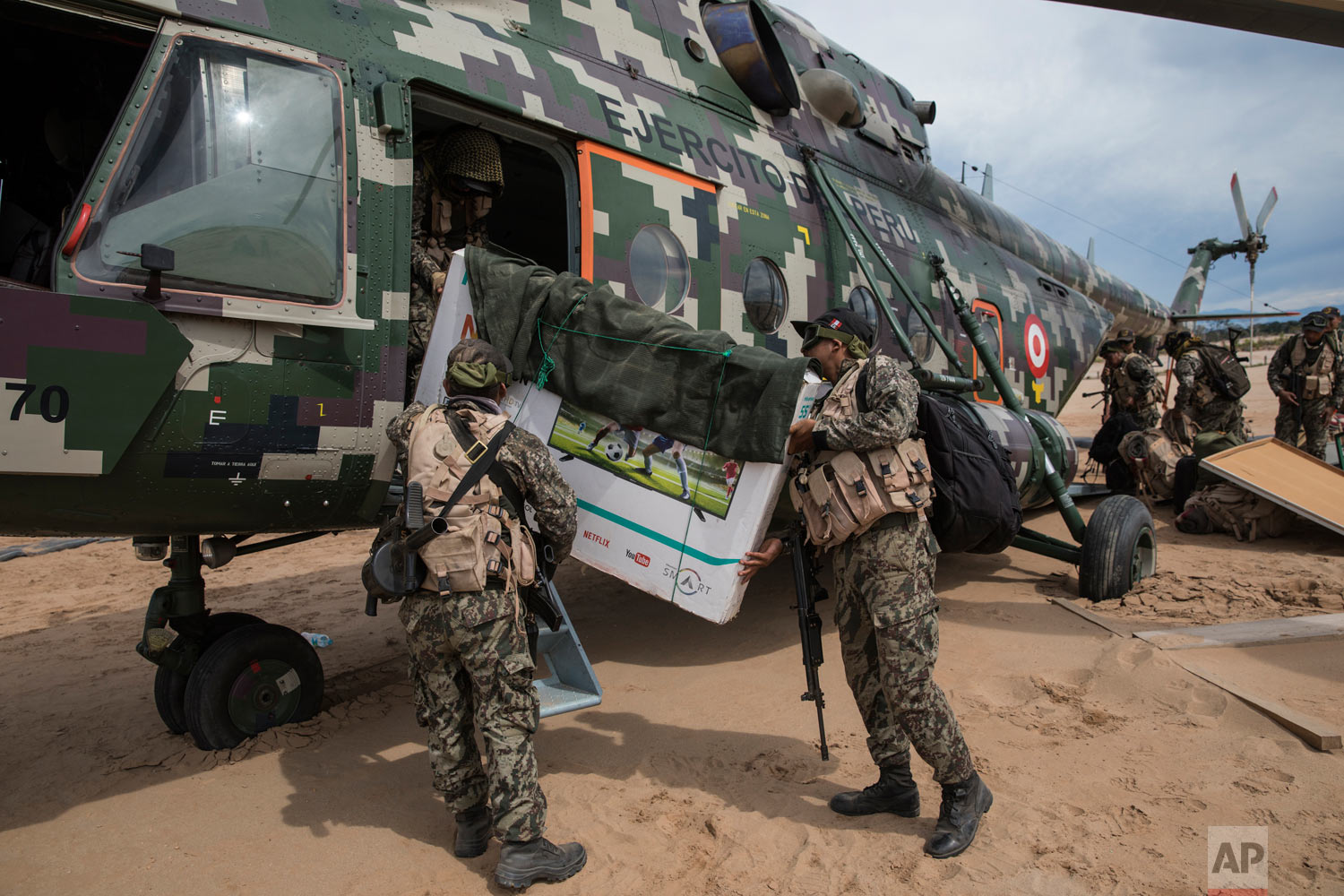 In this April 1, 2019 photo, returning to their home base soldiers load their television in to a military helicopter, on a makeshift airstrip at the Balata military and police base in Peru's Tambopata province. (AP Photo/Rodrigo Abd)