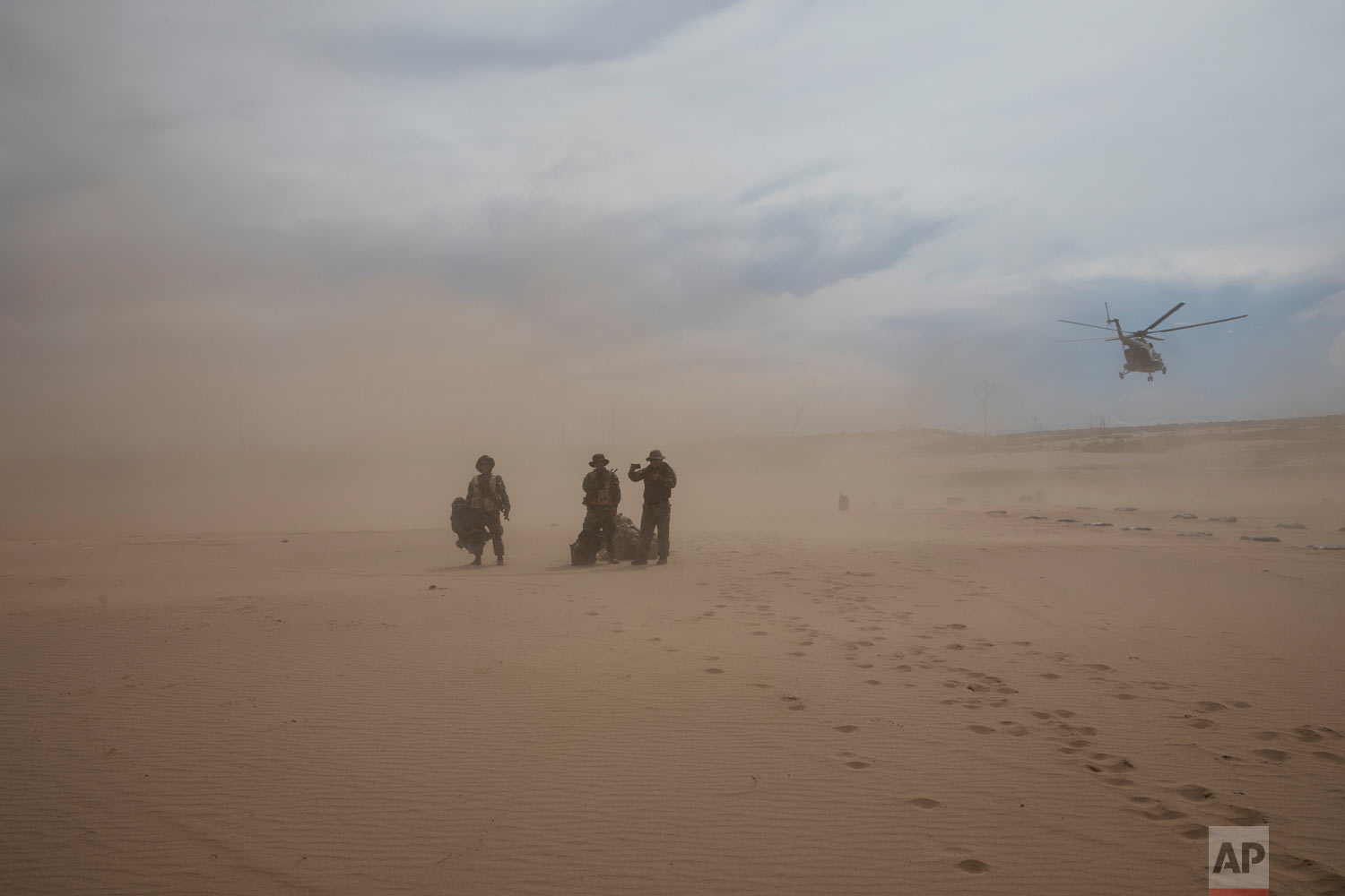 """Operation Mercury"" soldiers arrive for their new assignment stand in a dust cloud on a makeshift airstrip on April 1, 2019, at the Balata police and military base in Peru's Tambopata province, as the helicopter that brought them returns to the home base. (AP Photo/Rodrigo Abd)"
