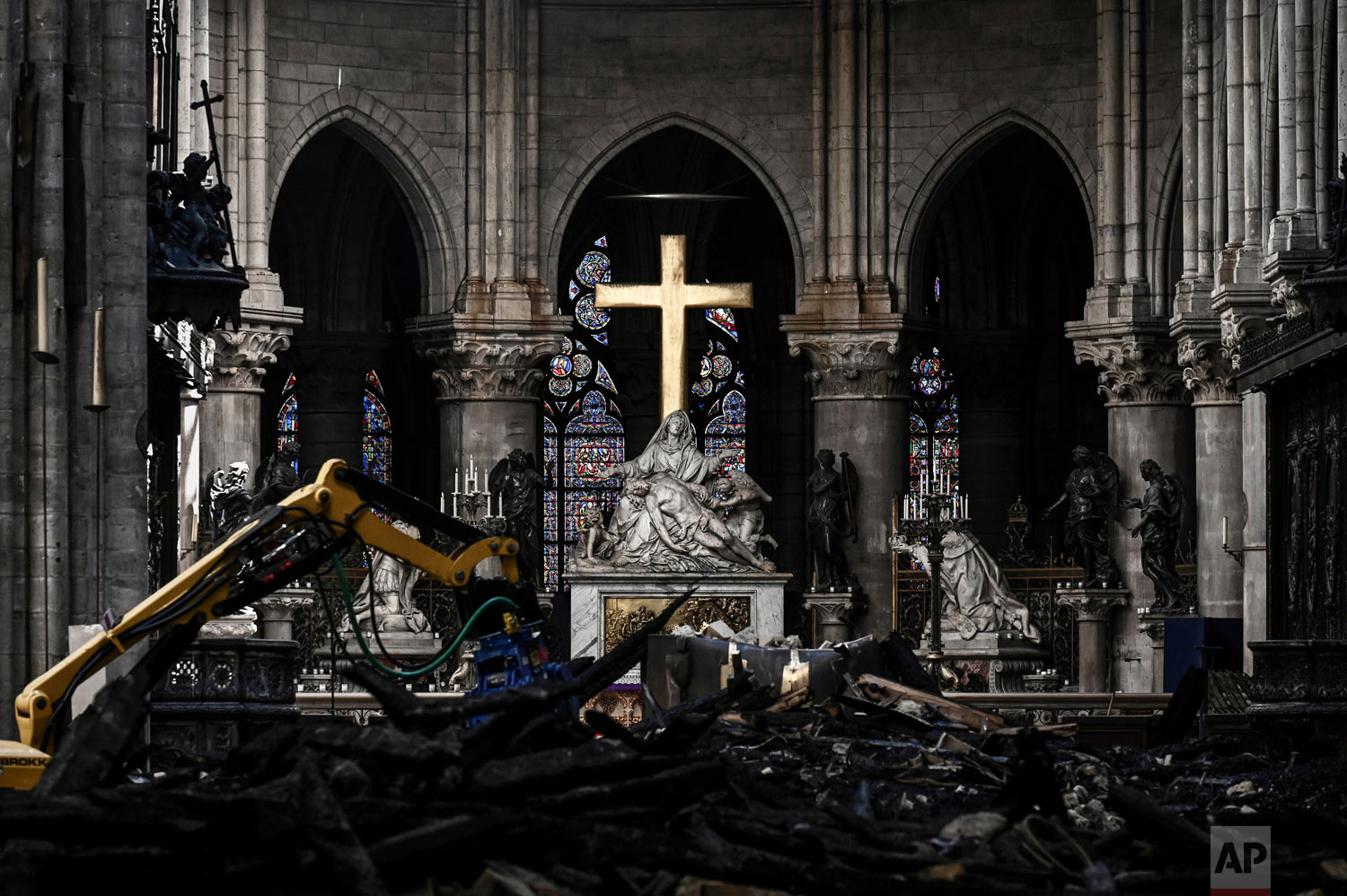 Rubble lies below the Pieta sculpture and a cross inside the Notre Dame de Paris cathedral on Wednesday May 15, 2019 in Paris. (Philippe Lopez/Pool via AP)