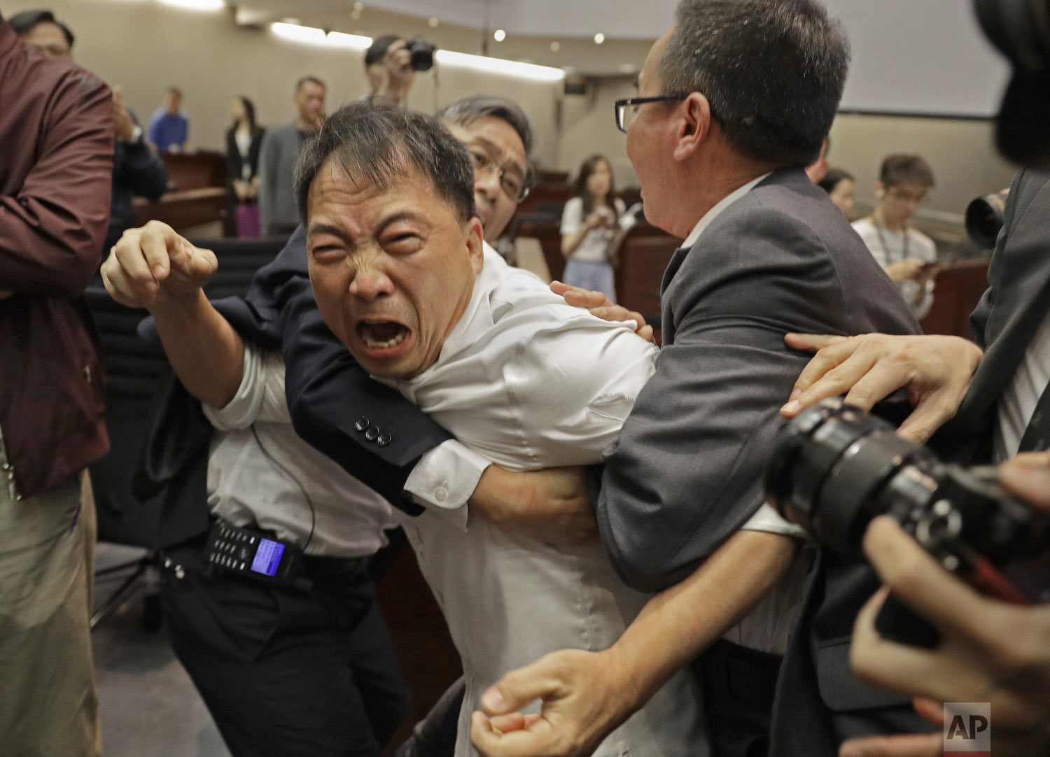 Pro-democracy lawmaker Wu Chi-wai, center, is restrained by security guards at the Legislative Council in Hong Kong, Saturday, May 11, 2019. Hong Kong's legislative assembly descended into chaos Saturday as lawmakers for and against controversial amendments to the territory's extradition law clashed over access to the chamber. (AP Photo/Vincent Yu)