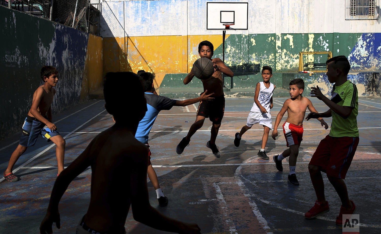 A group of boys play basketball at the Petare shantytown, in Caracas, Venezuela, Thursday, May 16, 2019. (AP Photo/Martin Mejia)