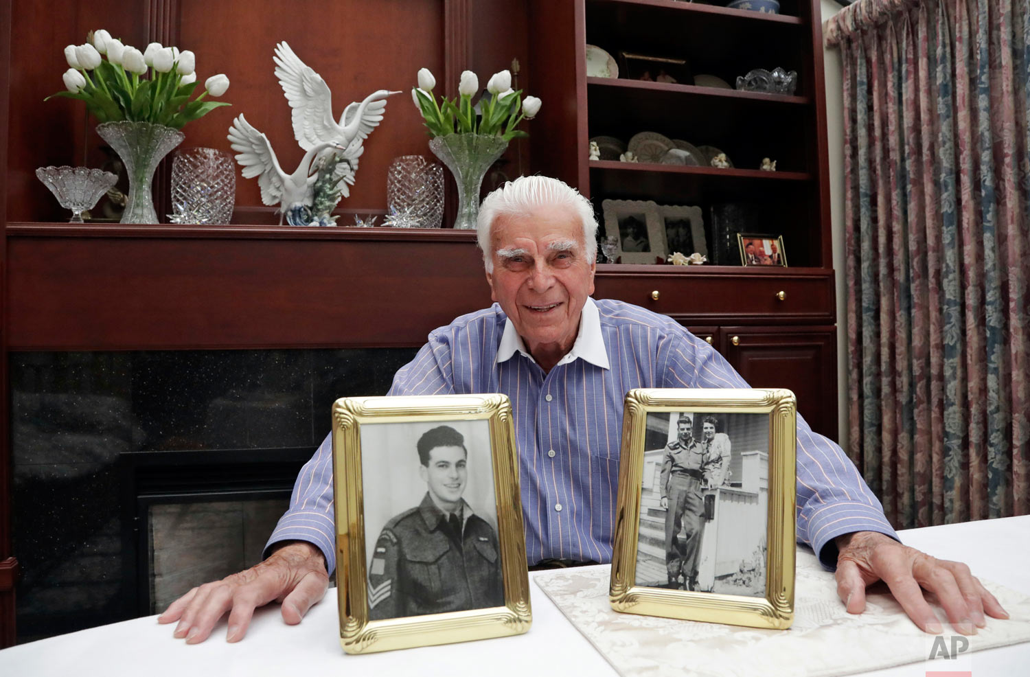 In this photo taken May 20, 2019, veteran Norman Harold Kirby sits with a photo of his mother, Katherine Louise Kirby, and himself, at 17, and a post-war portrait as he poses for a photo at his home in Lions Bay, Canada. The Canadian from British Columbia had joined the army when he was only 17 and was barely a 19-year-old private when he climbed into the landing craft that would take him to shore on June 6, 1944. (AP Photo/Elaine Thompson)