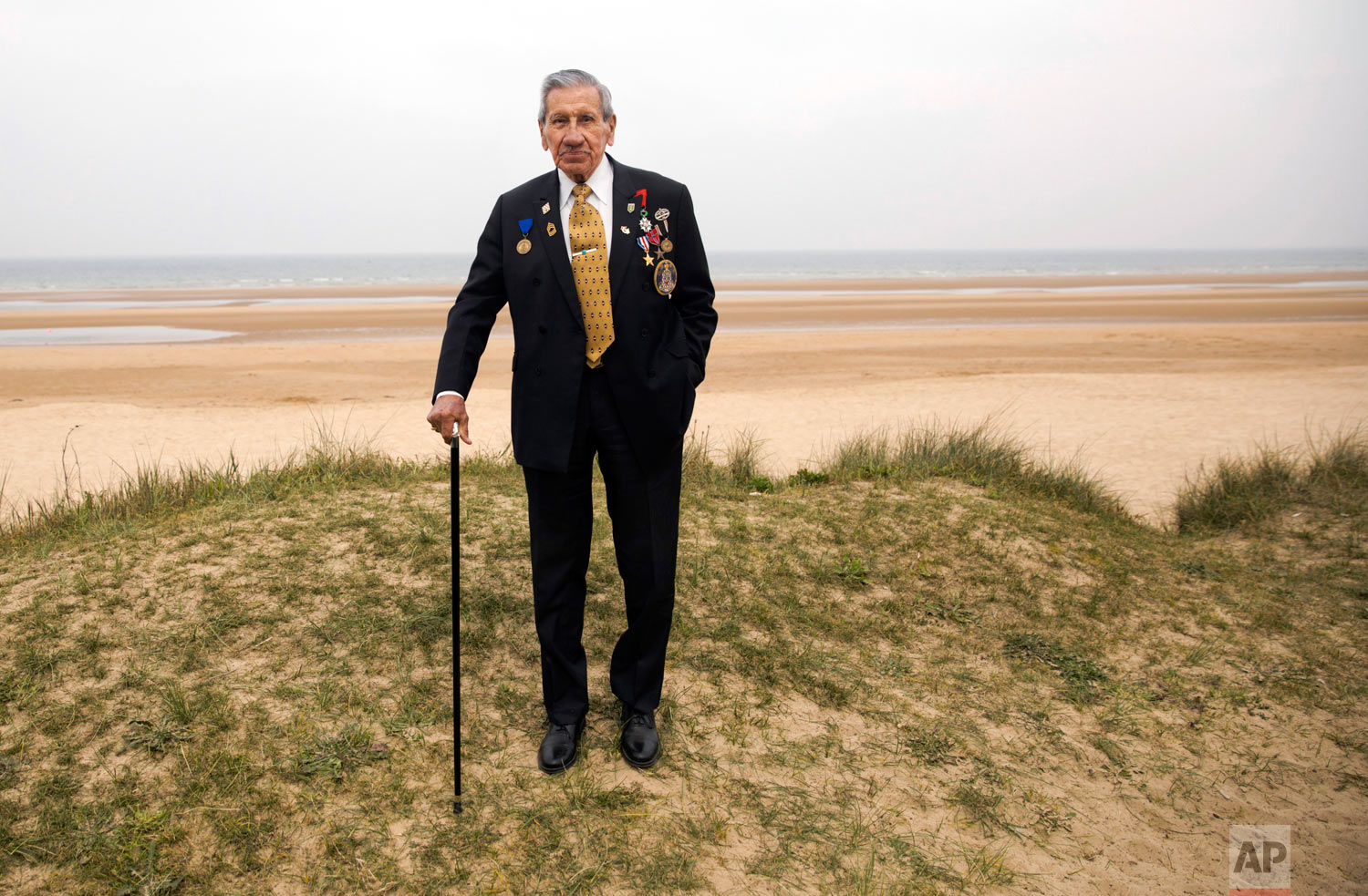 World War II and D-Day veteran Charles Norman Shay, from Indian Island, Maine, poses on a dune at Omaha Beach in Saint-Laurent-sur-Mer, Normandy, France, May 1, 2019. Shay was a combat medic on D-Day, assigned to an assault battalion in the first wave of attacks on D-Day, June 6, 1944. (AP Photo/Virginia Mayo)