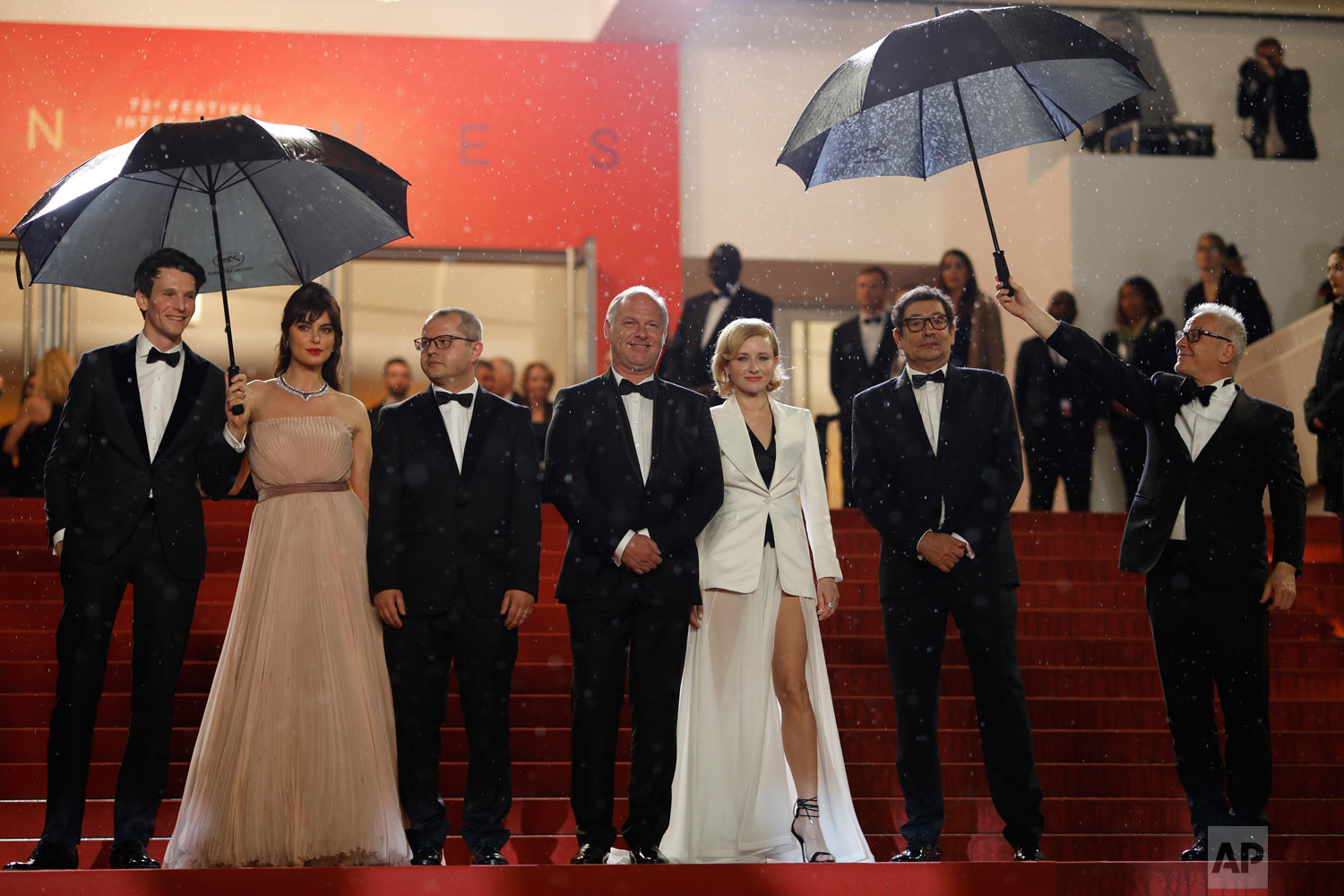 Actors Sabin Tambrea, Catrinel Marlon, director Corneliu Porumboiu, actors Vlad Ivanov, Rodica Lazar, Agusti Villaronga and Cannes film festival president Thierry Fremaux pose for photographers upon arrival at the premiere of the film 'The Whistlers' at the 72nd international film festival, Cannes, southern France, May 18, 2019. (AP Photo/Petros Giannakouris)