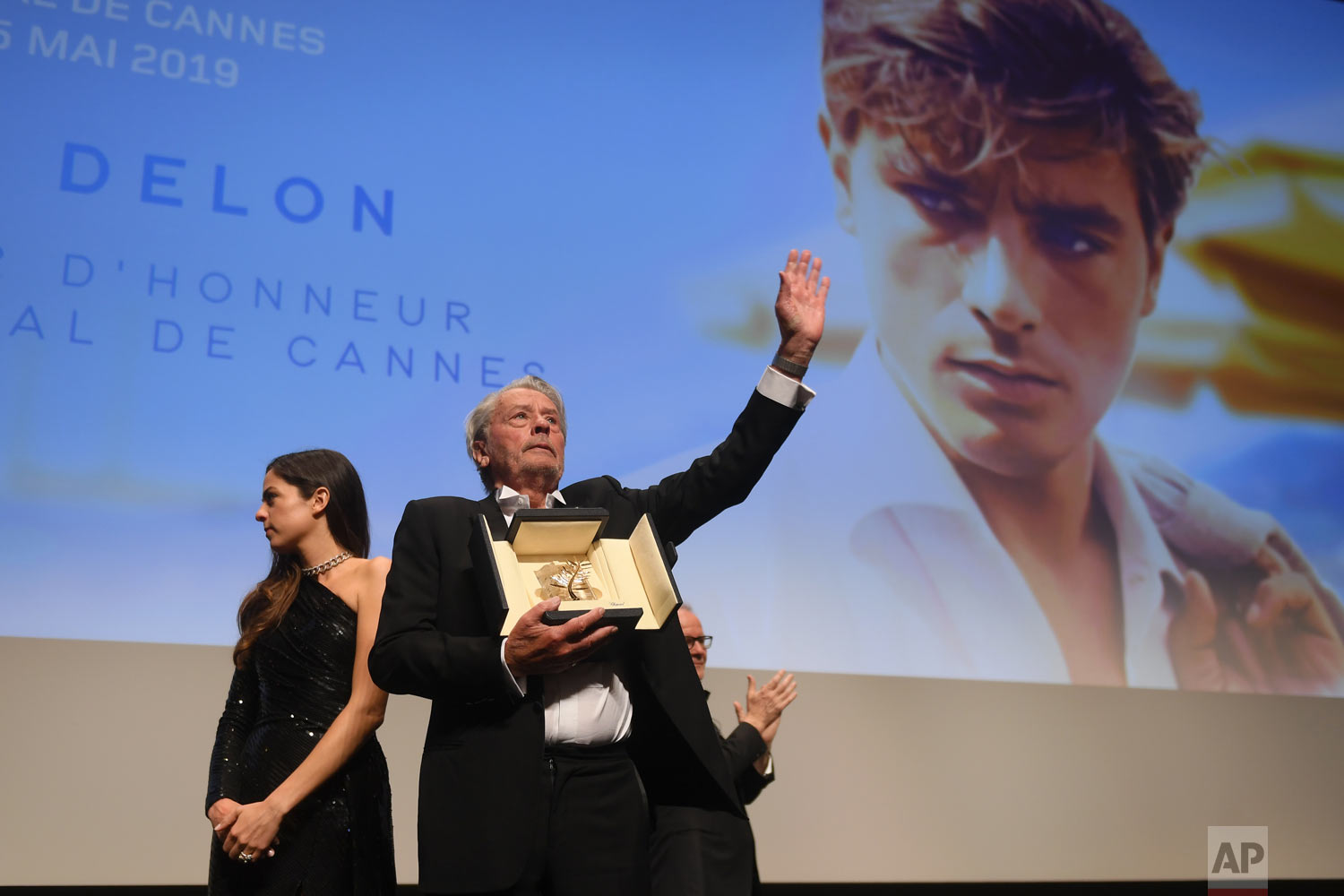 Alain Delon, centre, holds his honorary Palme D'Or award at the 72nd international film festival, Cannes, southern France, May 19, 2019. (Photo by Arthur Mola/Invision/AP)