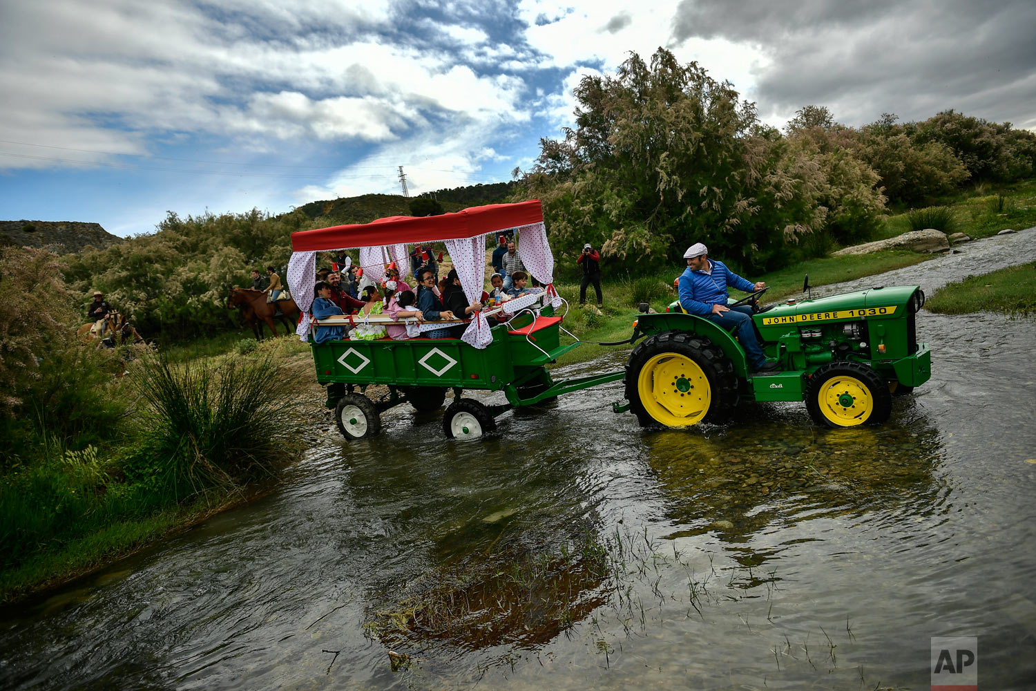 "Devotees of the Rocio Virgin cross a river as they take part in the ""Romeria de El Rocio"" in the countryside outside Fitero, northern Spain, May 25, 2019. (AP Photo/Alvaro Barrientos)"