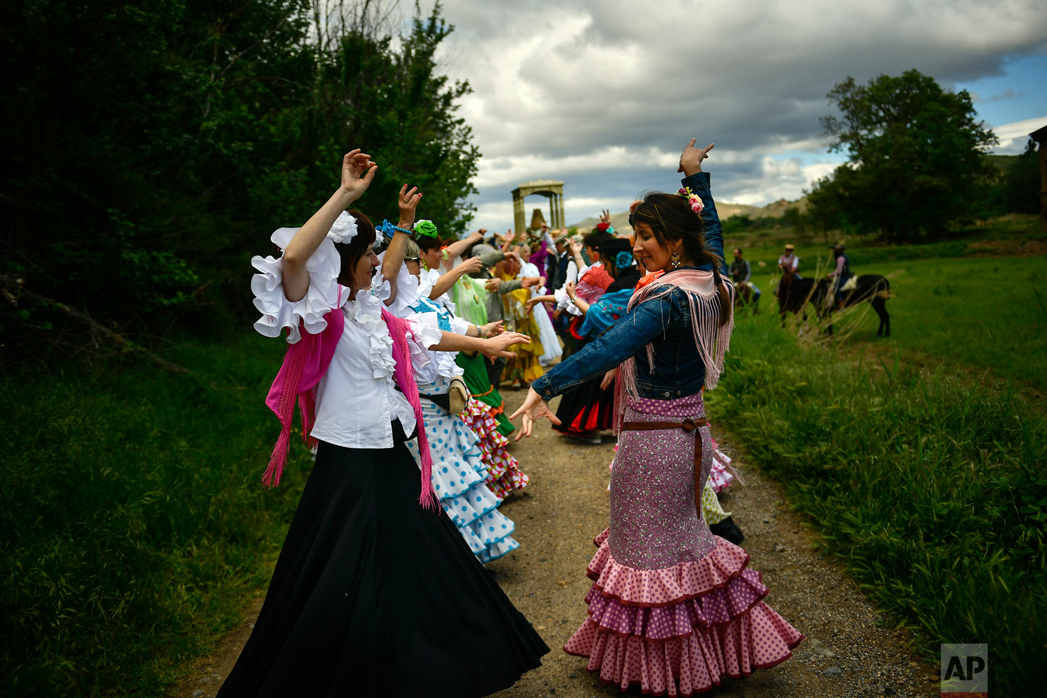 "Devotees of the Rocio Virgin dance while taking part in the ""Romeria de El Rocio"" in the countryside outside Fitero, northern Spain, May 25, 2019. (AP Photo/Alvaro Barrientos)"