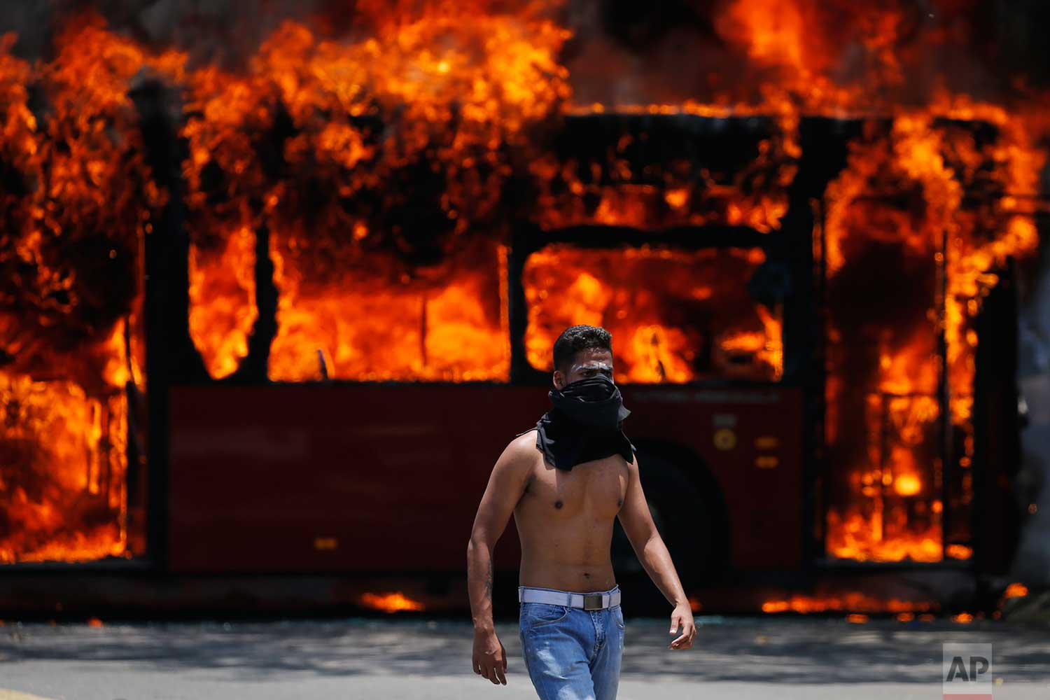 An anti-government protester walks near a bus that was set on fire by opponents of Venezuela's President Nicolas Maduro during clashes between rebel and loyalist soldiers in Caracas, Venezuela, Tuesday, April 30, 2019. Venezuelan opposition leader Juan Guaido took to the streets with a small contingent of heavily armed troops early Tuesday in a bold and risky call for the military to rise up and oust Maduro. (AP Photo/Fernando Llano)