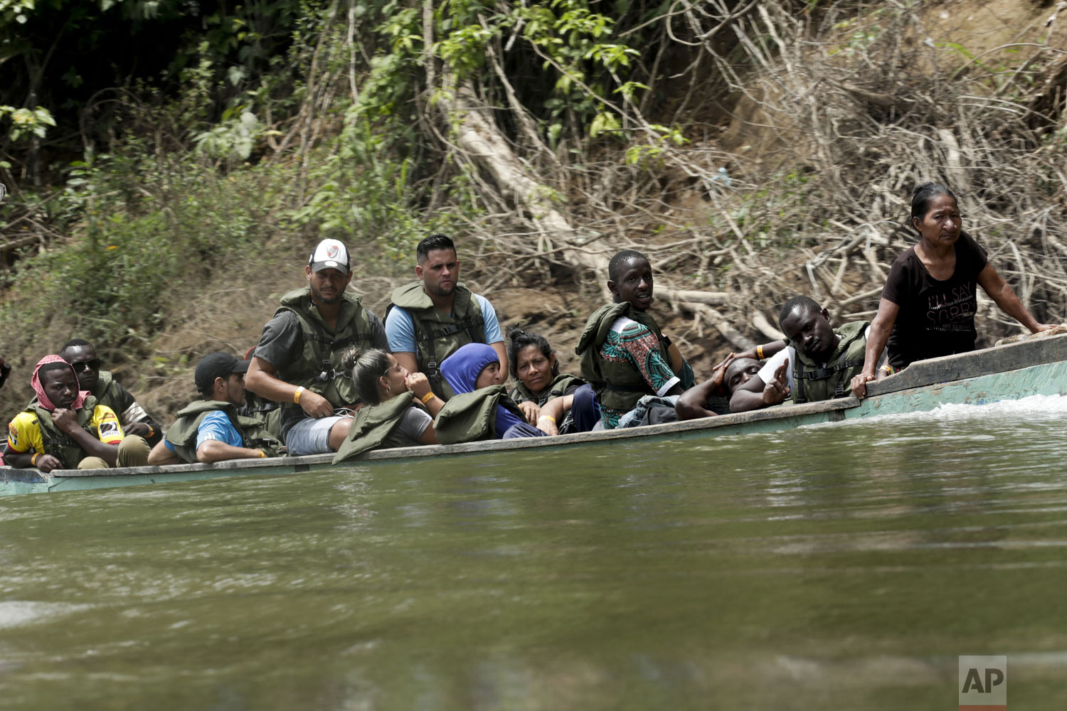 Migrants travel on a dangerously overloaded boat, on the Tuquesa river on their way to Peñitas, from Bajo Chiquito, Darien province, Panama, on Saturday, May 25, 2019. After trekking for days from Colombia, migrants arriving at Bajo Chiquito, feel relief. It's a place to rest, seek sustenance, communicate with loved ones to let them know they're OK and recover their strength, but ahead lies one last trek to safety by boat or by foot. (AP Photo/Arnulfo Franco)