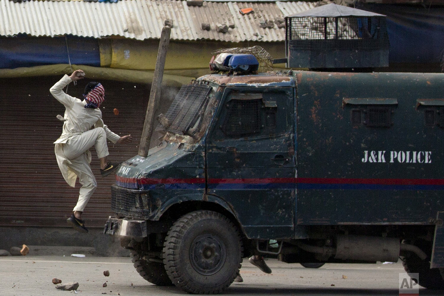 A masked Kashmiri protester jumps on an Indian police armored vehicle as he throw stones at it during a protest in Srinagar, Indian-controlled Kashmir, on Friday, May 31, 2019. Government forces fired tear gas and pellets to disperse hundreds protesting the recent killing of a Kashmiri rebel leader, coinciding with the annual Al-Quds Day demonstration. The last Friday of the Islamic holy month of Ramadan is observed in many Muslim communities as Al-Quds Day, or Jerusalem Day, as a way of expressing support to the Palestinians and emphasizing the importance of Jerusalem to Muslims. (AP Photo/Dar Yasin)