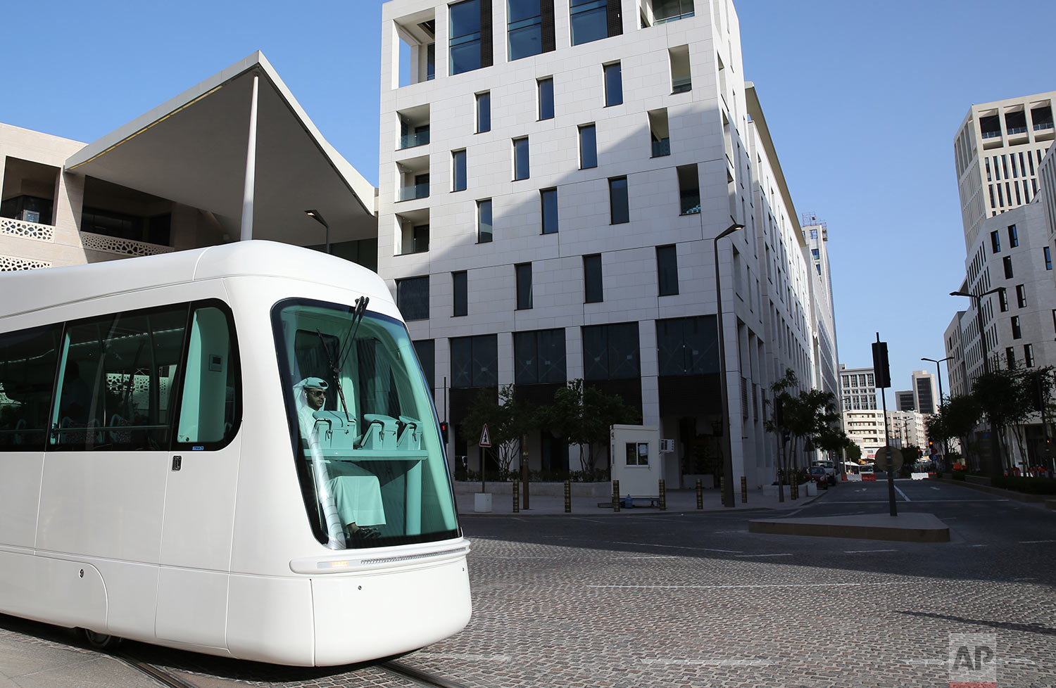 In this Wednesday, April 24, 2019 photo, Mohammed, an Iranian origin Qatari tram driver, born and raised in Qatar, drives during a trial session at the Musheireb Downtown Doha district, Qatar.  (AP Photo/Kamran Jebreili)